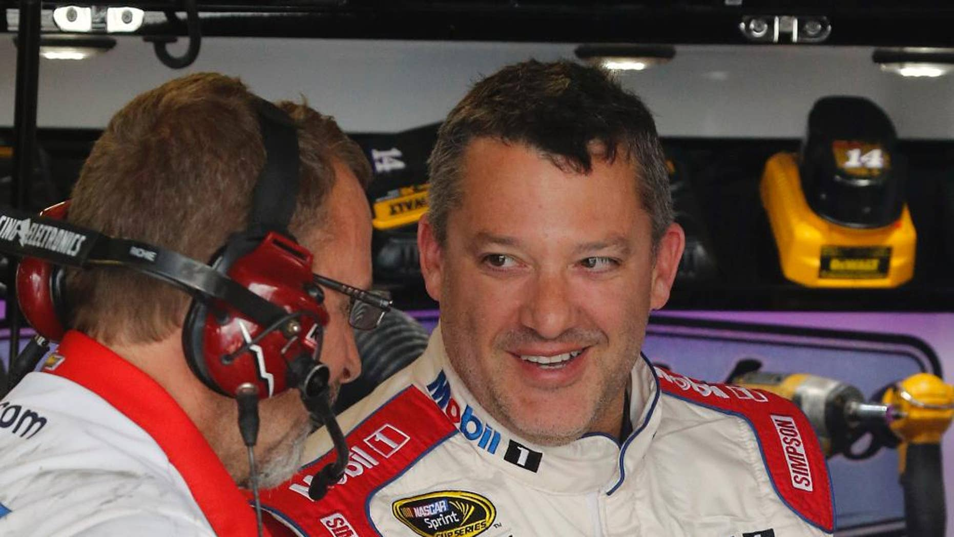 FILE - In this April 22, 2016, file photo, Tony Stewart, right, jokes with a crew member during practice for a NASCAR Sprint Cup auto race at Richmond International Raceway in Richmond, Va. Now that he's got his first victory in over three years, Stewart is able to realistically set some goals for his final season as a NASCAR driver. First up: Cross Kentucky Speedway off the list of active tracks where he's never won. (AP Photo/Steve Helber, File)