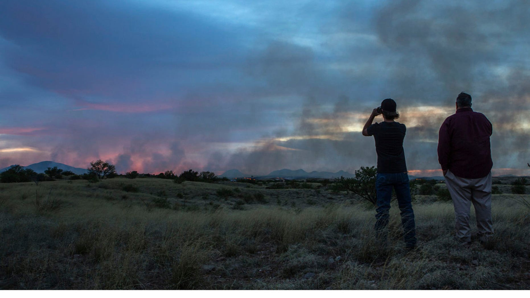 In this Monday, April 24, 2017 photo, people watch the Sawmill Fire from Las Cienegas Conservation Area north of Sonoita, Ariz.