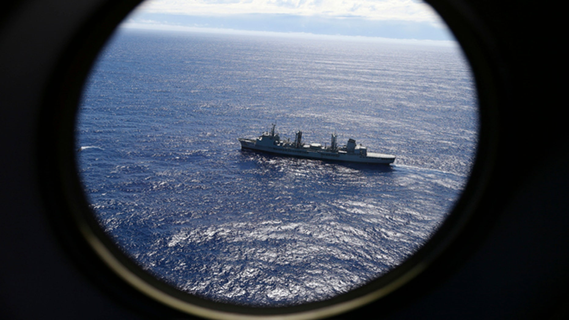FILE - In this March 31, 2014, file photo, HMAS Success scans the southern Indian Ocean, near the coast of Western Australia, as a Royal New Zealand Air Force P3 Orion flies over, while searching for missing Malaysia Airlines Flight MH370.