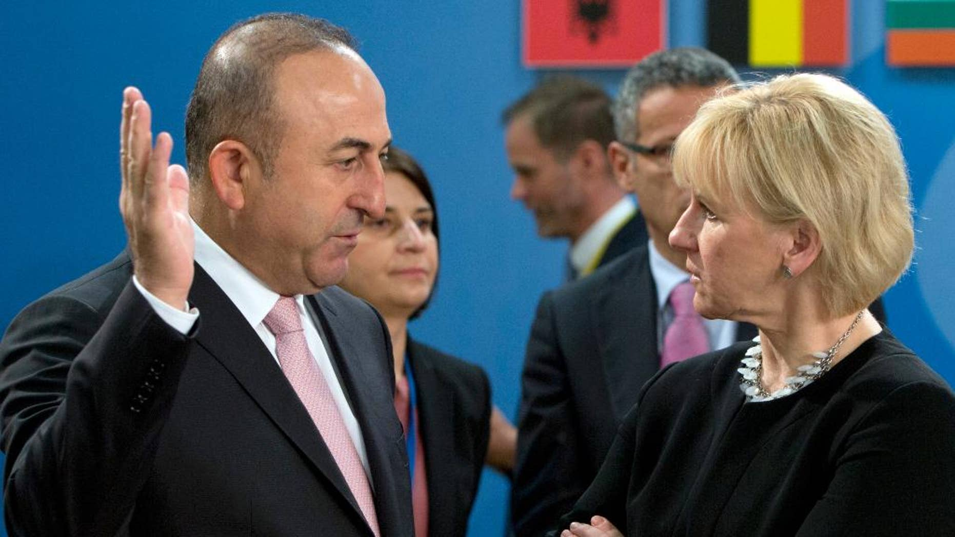 FILE- In this Friday, May 20, 2016 file photo, Turkish Foreign Minister Mevlut Cavusoglu, left, speaks with Swedish Foreign Minister Margot Wallstrom during a meeting of the North Atlantic Council at NATO headquarters in Brussels. Turkey has summoned on Monday, Aug. 15, 2016, officials from Austria and Sweden to protest against news reports and Twitter comments in the two countries relating to a Turkish Constitutional Court ruling on child abuse. (AP Photo/Virginia Mayo, File)
