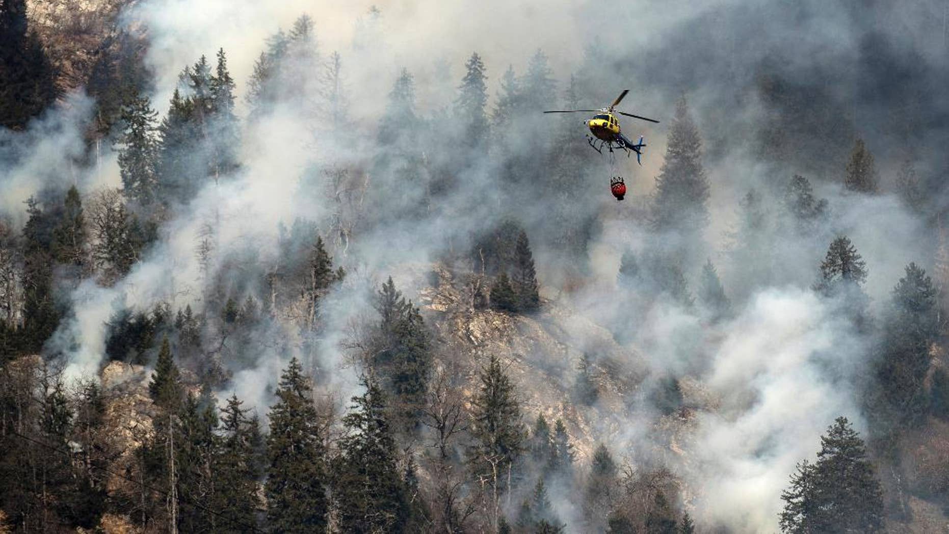 A fire fighting helicopter discharges water over the forest fires near Mesocco in Southern Switzerland, Wednesday, Dec.  28, 2016. (Gabriele Putzu/Keystone,Ti-Press via AP)