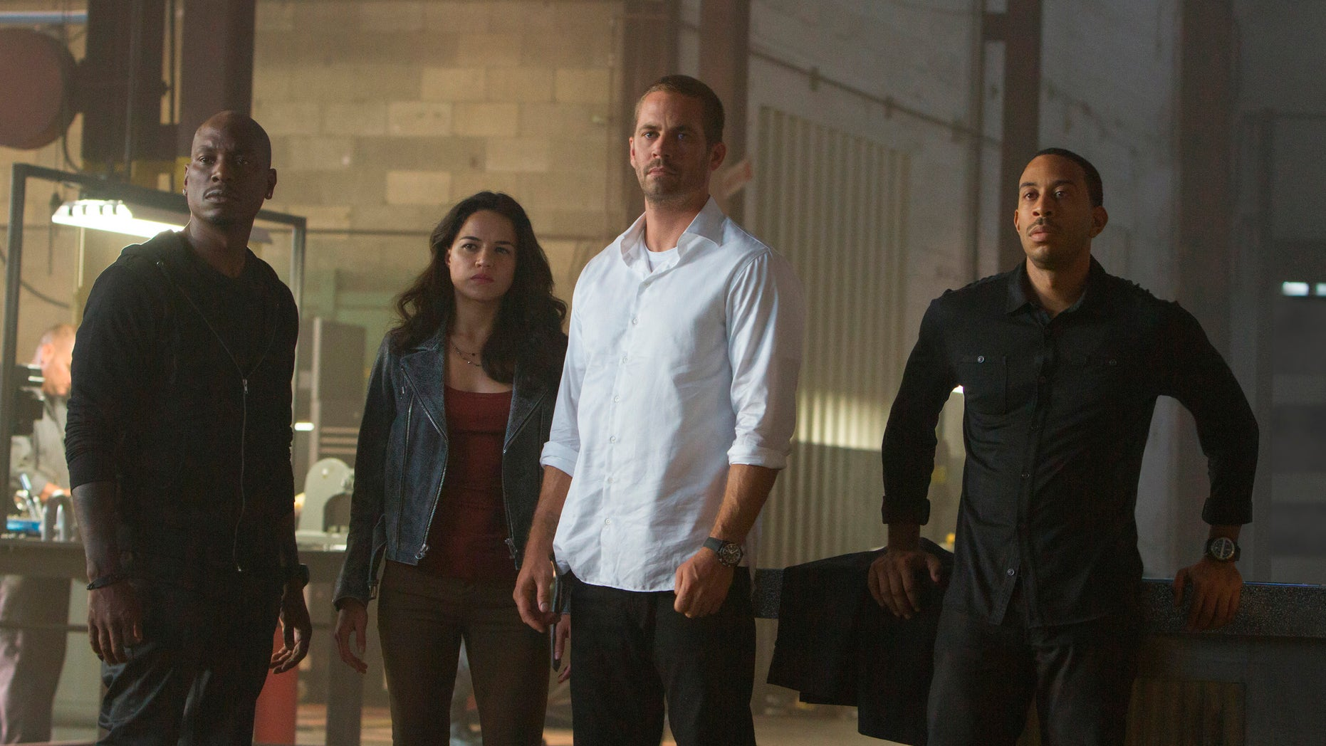 "This photo provided by Universal Pictures shows, from left, Tyrese Gibson as Roman, Michelle Rodriguez as Letty, Paul Walker as Brian, and Chris Ludacris as Tej, in a scene from ""Furious 7.""  (AP Photo/Universal Pictures, Scott Garfield)"