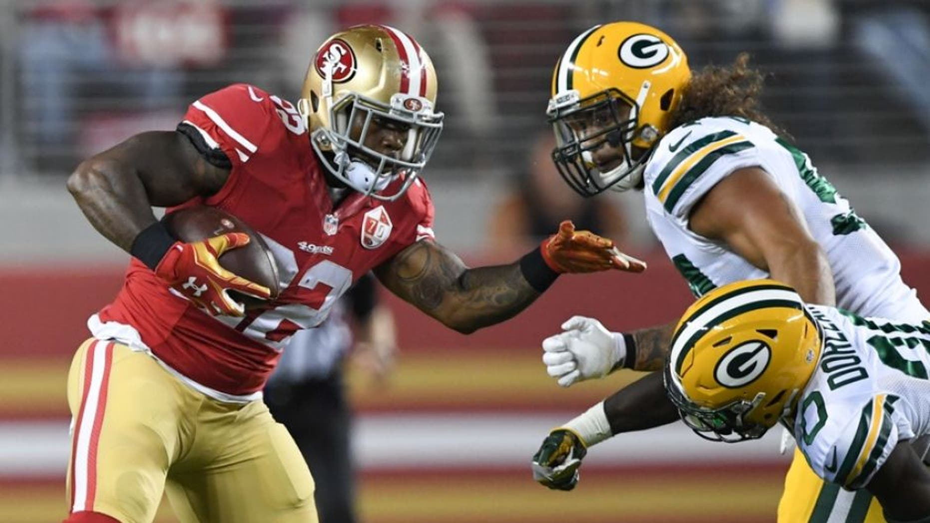 August 26, 2016; Santa Clara, CA, USA; San Francisco 49ers running back Mike Davis (22, left) runs the football against Green Bay Packers defensive back Makinton Dorleant (20) during the third quarter at Levi's Stadium. Mandatory Credit: Kyle Terada-USA TODAY Sports