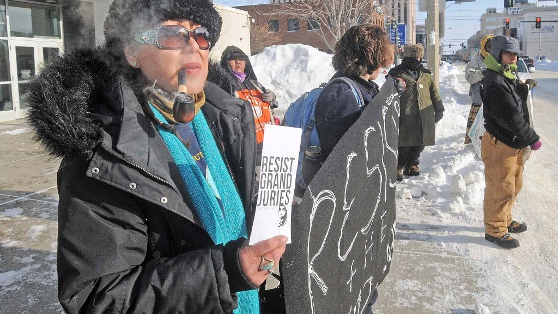 Vivian Billy, left, was outside the Federal Building in downtown Bismarck on Wednesday, Jan. 4, 2017, handing out resist grand jury pamphlets while helping hold a banner with other protesters against the Dakota Access Pipeline. (Tom Stromme/The Bismarck Tribune via AP)