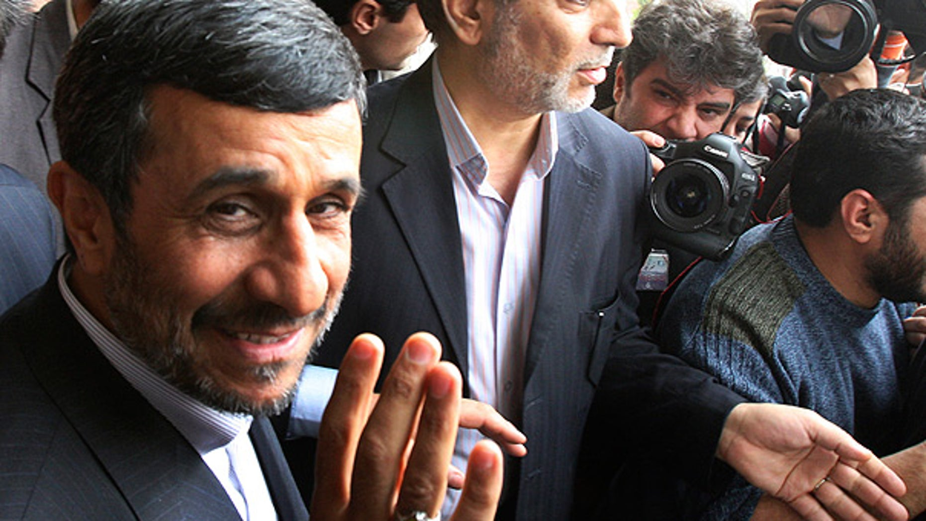 Feb. 20: Iranian President Mahmoud Ahmadinejad waves to the media as he leaves the parliament in Tehran.