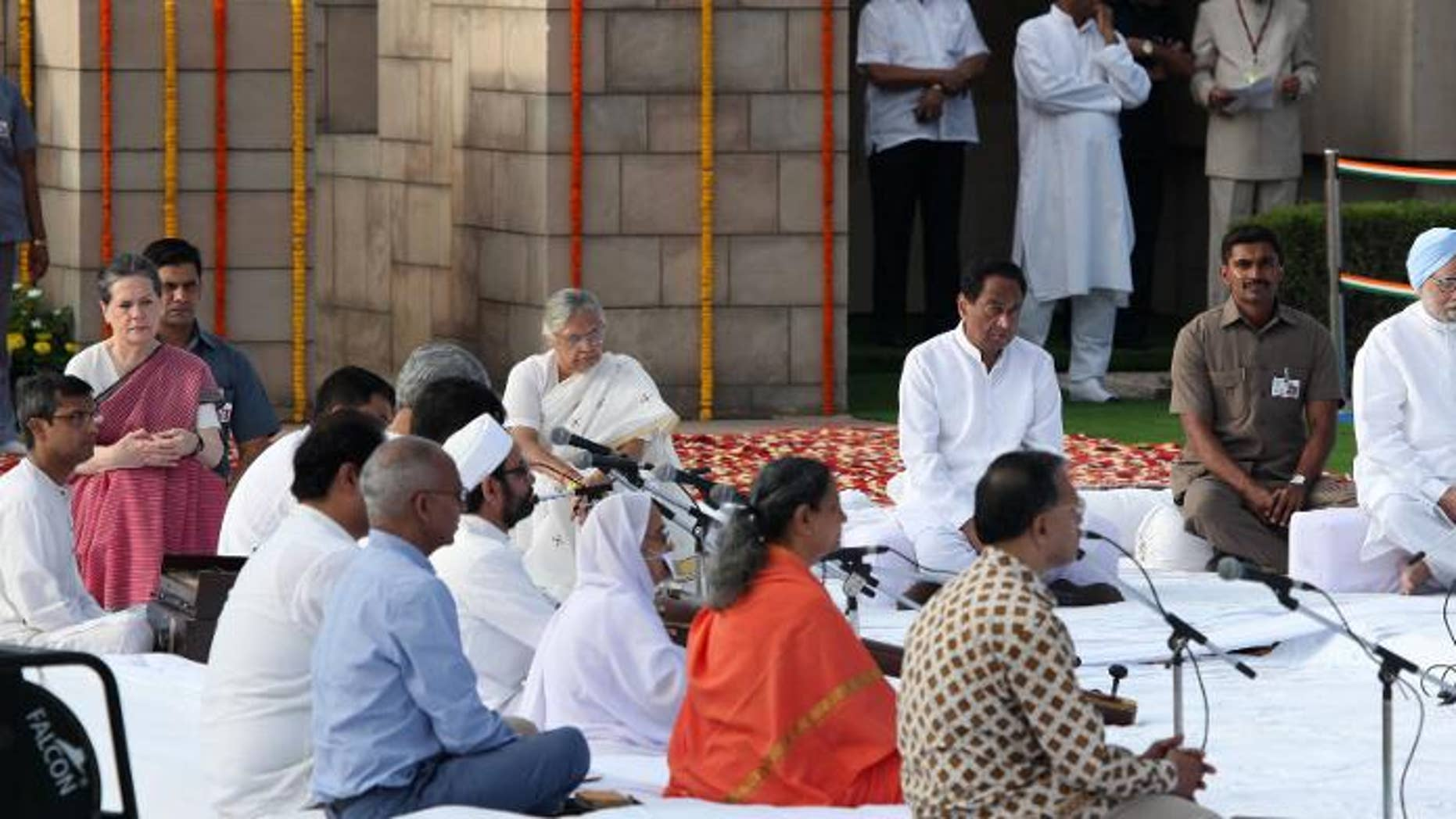 Chairperson of the Congress-led UPA government, Sonia Gandhi (L) and Indian Prime Minister Manmohan Singh (R) paying their respects at the memorial to the Father of the Nation Mahatma Gandhi at Rajghat in New Delhi on October 2, 2013