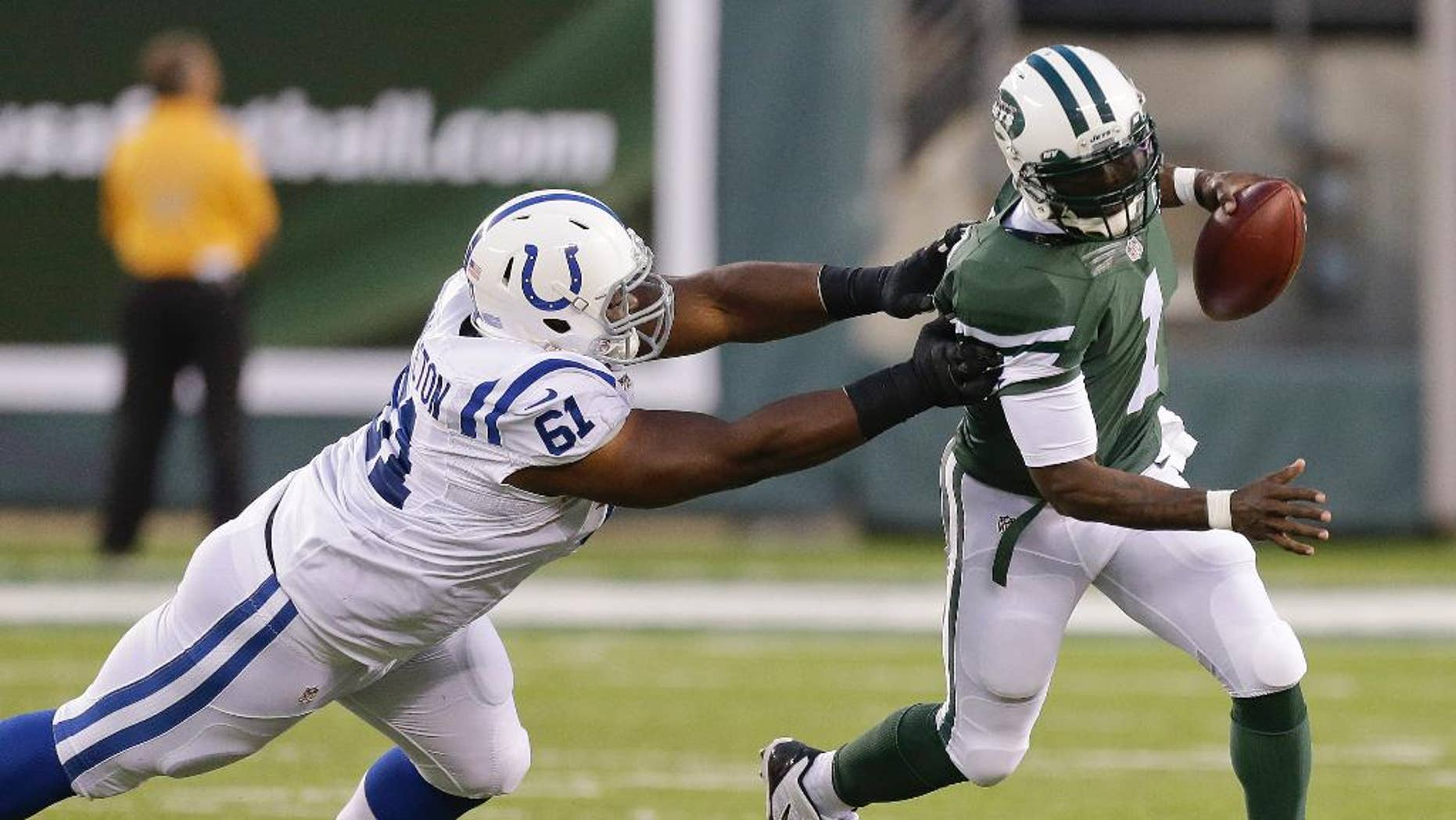New York Jets quarterback Michael Vick (1) avoids Indianapolis Colts defensive tackle Jeris Pendleton (61) in the second quarter of a preseason NFL football game, Thursday, Aug. 7, 2014, in East Rutherford, N.J. (AP Photo/Frank Franklin II)