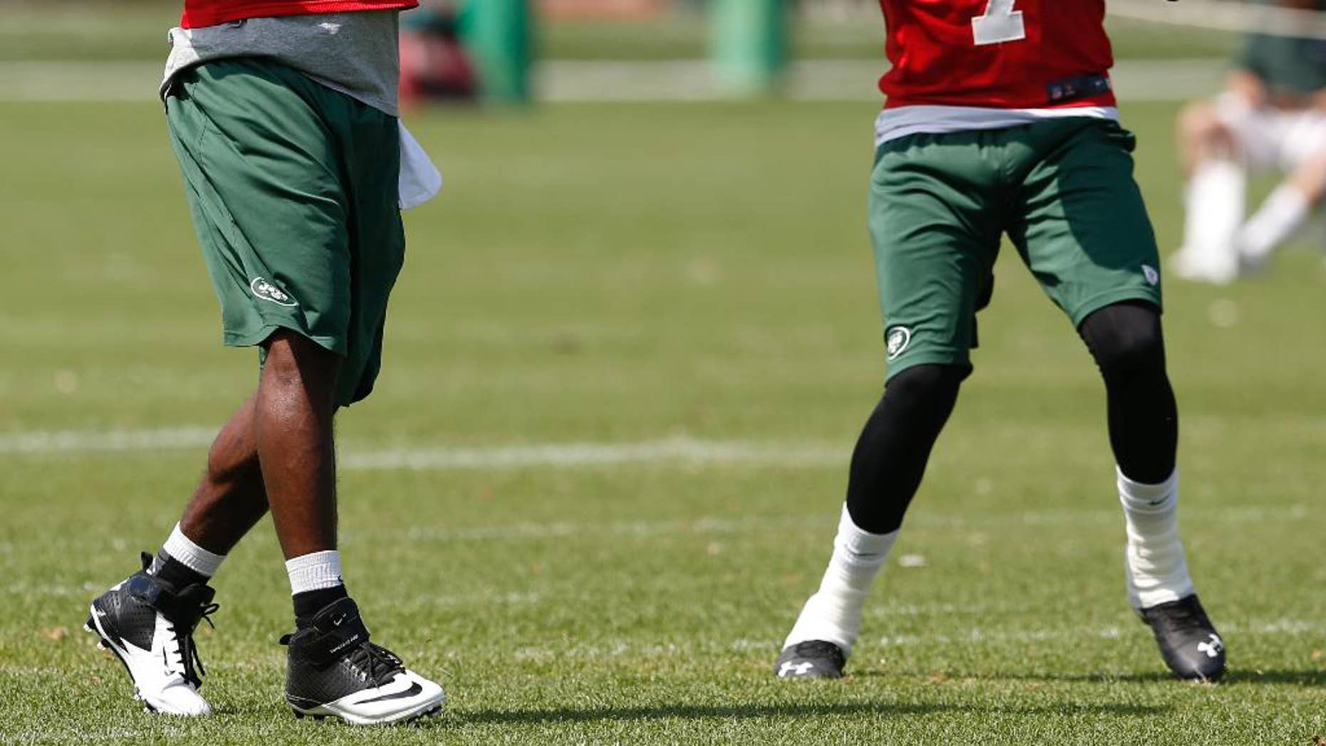 New York Jets quarterbacks Michael Vick, left, and Geno Smith work out during an NFL football organized team activity, Wednesday, June 4, 2014, in Florham Park, N.J. (AP Photo/Julio Cortez)