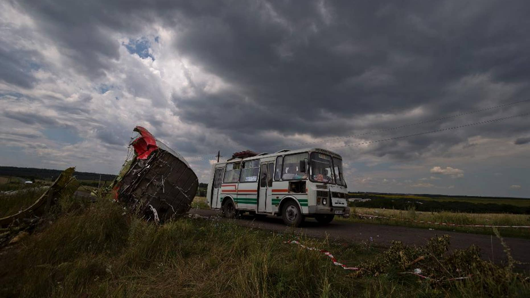 A commuter bus drives by aircraft wreckage at the crash site of Malaysia Airlines Flight 17 near the village of Hrabove, eastern Ukraine, Tuesday, July 22, 2014. A team of Malaysian investigators visited the site along with members of the OSCE mission in Ukraine for the first time since the air crash last week.(AP Photo/Vadim Ghirda)