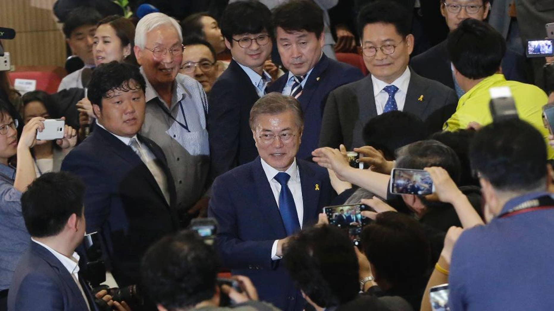 South Korea's presidential candidate Moon Jae-in, center, of the Democratic Party is celebrated by his party leaders and members as they watch the local media's results of exit polls for the presidential election on television in Seoul, South Korea, Tuesday, May 9, 2017. Exit polls forecast that liberal candidate Moon will win the election Tuesday to succeed ousted President Park Geun-hye. (AP Photo/Ahn Young-joon)