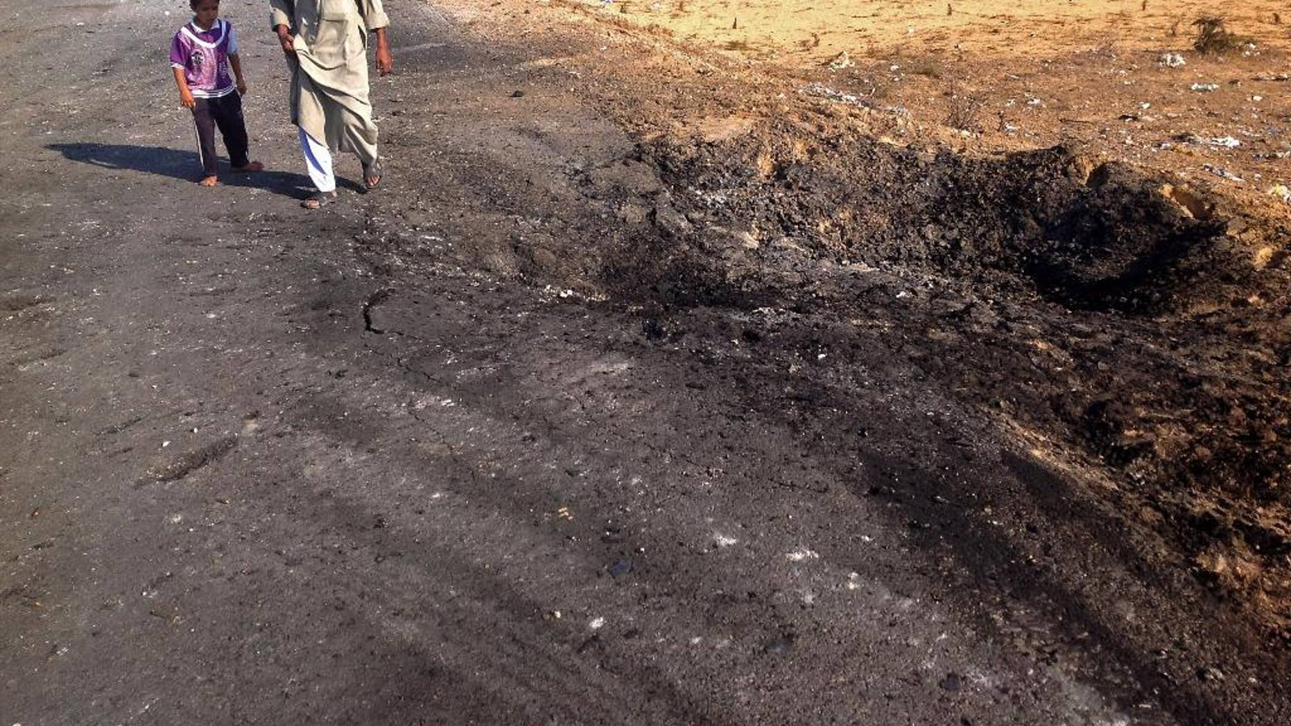 FILE - In this Nov. 20, 2013 file photo, a man and child walk past a crater from a suicide car bomb attack on the road between the border town of Rafah and the coastal city of el-Arish, Egypt. Egyptian authorities on Tuesday, Oct. 28, 2014, ordered residents living along the country's eastern border with the Gaza Strip to evacuate so they can demolish their homes and set up a buffer zone to stop weapons and militant trafficking between Egypt and the Palestinian territory, officials said. The measure comes four days after militants attacked an army post, killing at least 31 soldiers in the restive area in the northeastern corner of the Sinai Peninsula. (AP Photo/Ahmed Abu Deraa, File)