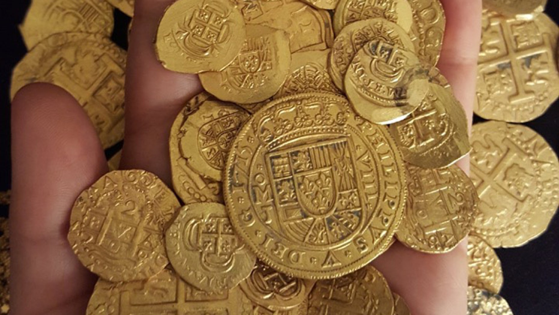 This undated photo made available by the 1715 Fleet-Queens Jewels, LLC., shows gold chains and coins that were recovered together with a royal coin off the coast of Florida. A family of treasure hunters has found more than $1 million worth of gold artifacts in the Atlantic Ocean off Fort Pierce, Fla., announced Monday, July 27, 2015. (1715 Fleet-Queen Jewels, LLC via AP)