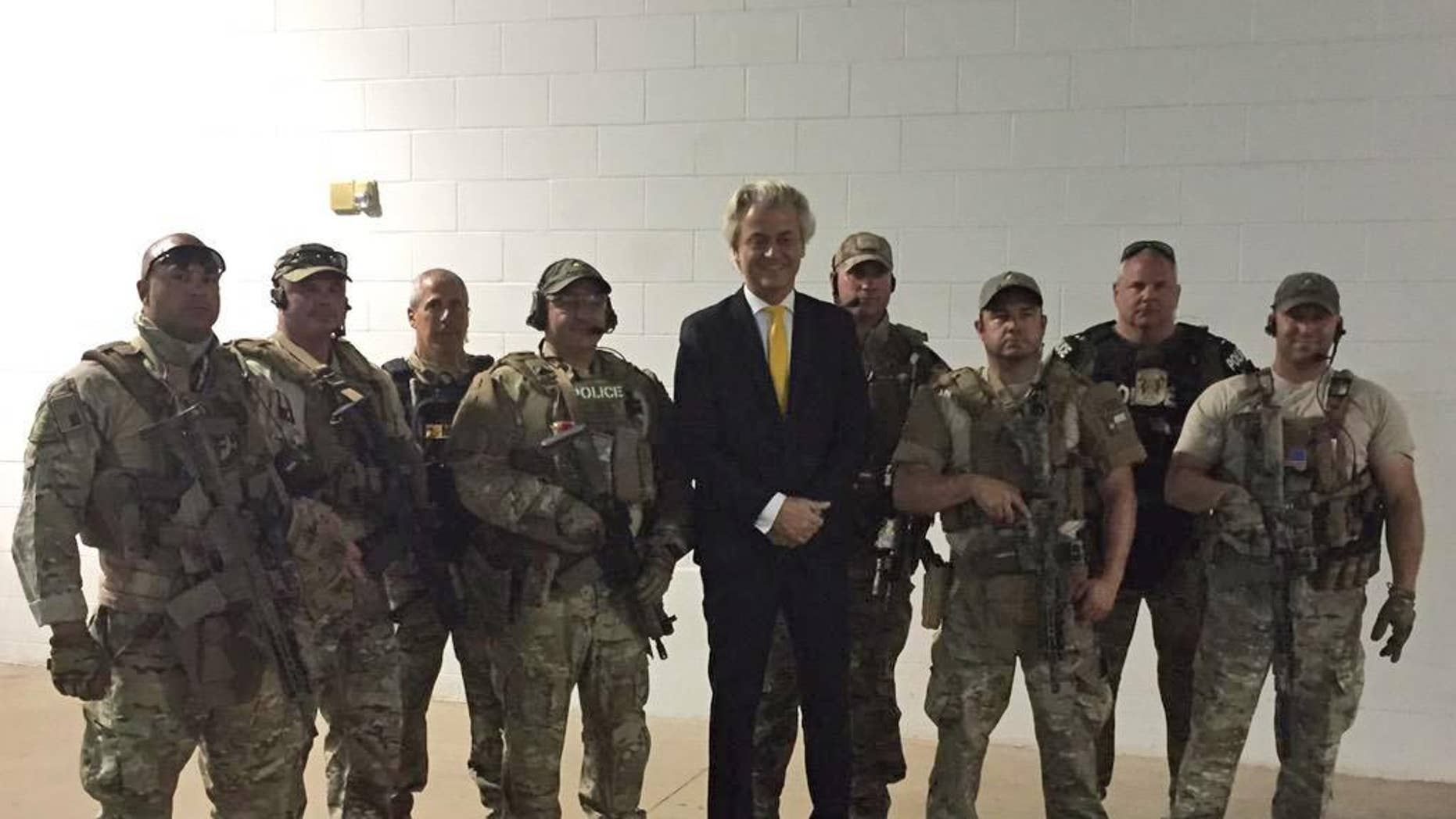 In this photo provided on Monday, May 4, 2015 by Geert Wilders, Dutch lawmaker Geert Wilders, leader of the anti-Islam Freedom Party, center, poses for a photograph with police officers who responded to a shooting outside a provocative contest for cartoon depictions of Prophet Muhammad in Garland, Texas. Two gunmen were killed Sunday, May 3, 2015 in Texas after opening fire on a security officer outside a provocative contest for cartoon depictions of Prophet Muhammad, and a bomb squad was called in to search their vehicle as a precaution, authorities said. (Geert Wilders via AP)