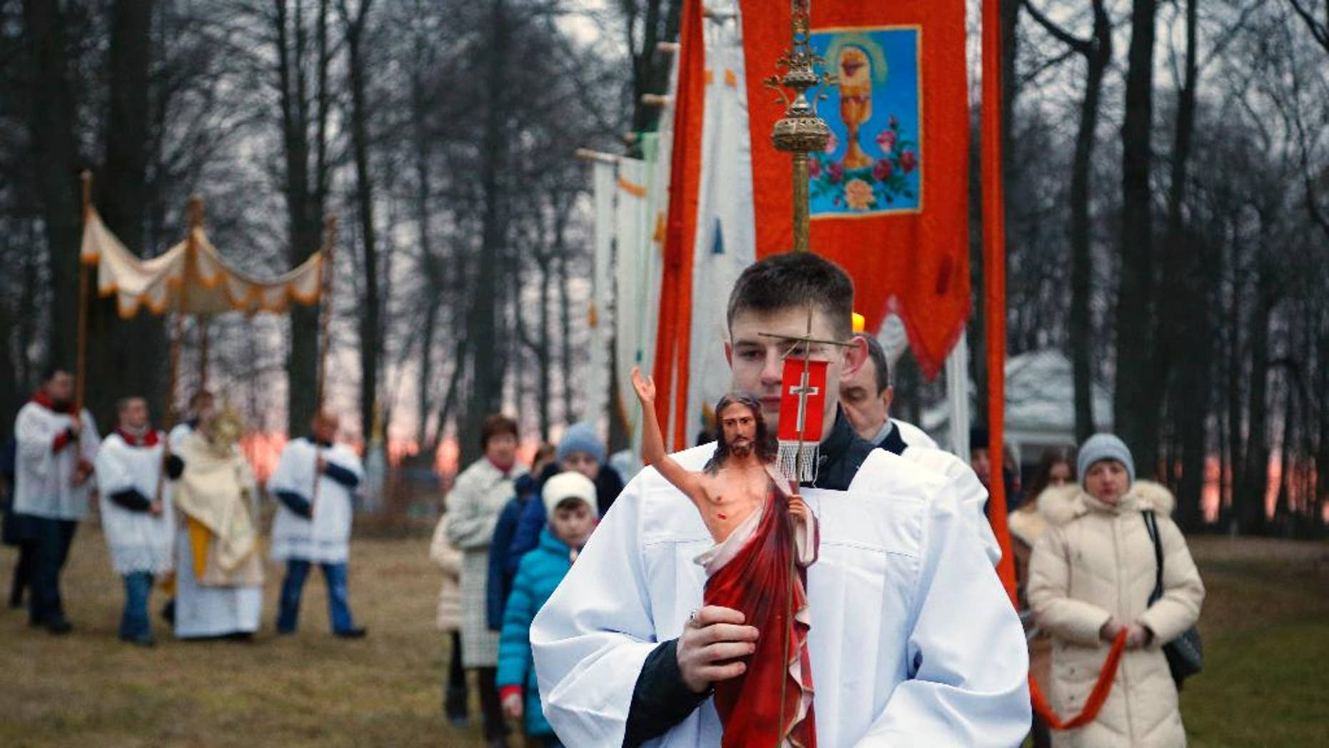 Devotees carry gonfalons during Easter Sunday rites in the village of Vselyub, 150 kilometers (93 miles) west of Minsk, Belarus, Sunday, March 27, 2016. (AP Photo/Sergei Grits)