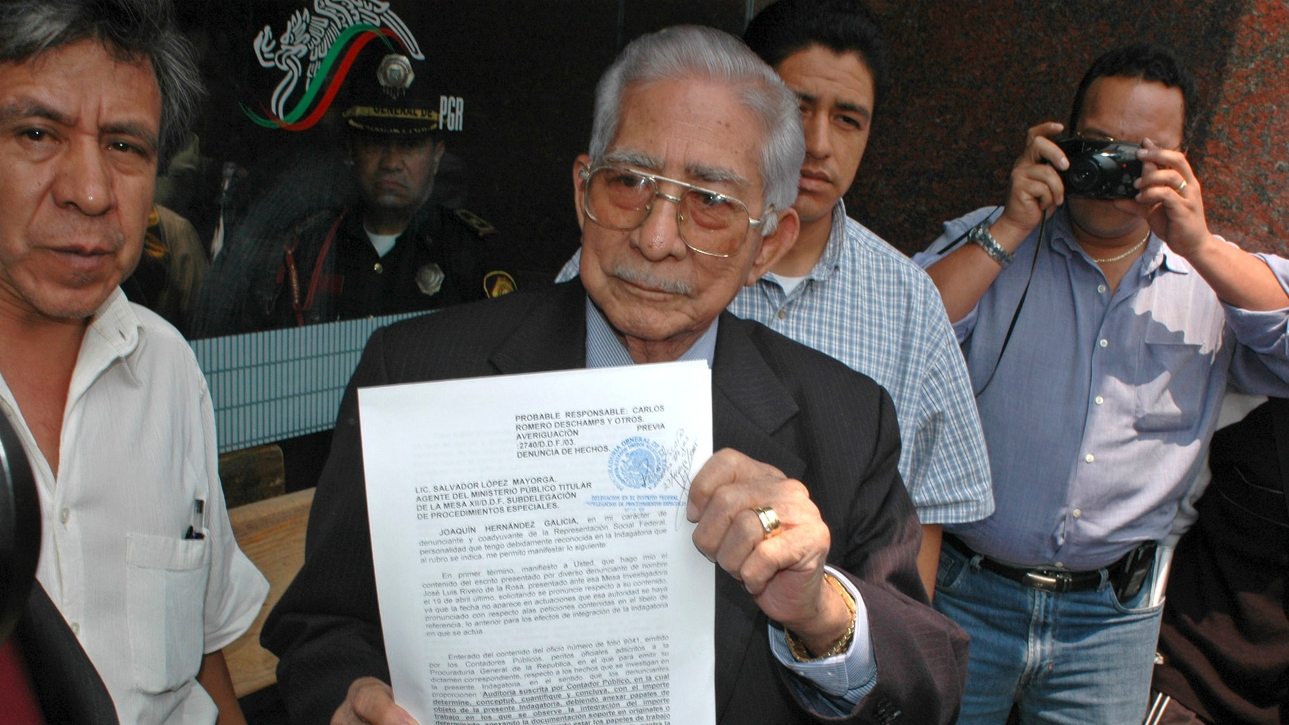 "FILE - In this May 27, 2005 file photo, the former boss of Mexico's powerful oil workers union, Joaquin Hernandez Galicia, holds up a lawsuit on corruption charges he filed against the current union boss of Pemex outside a courthouse in Mexico City. Hernandez was an old-style Mexican labor leader who became one of the country's most powerful and wealthiest men through patronage, corruption and strong-arm tactics. A son of the once-feared boss says Hernandez, known as ""La Quina,"" has died after spending several days in a hospital in the northern city of Tampico for stomach problems. He was 91. (AP Photo/Roberto Velazquez, File)"