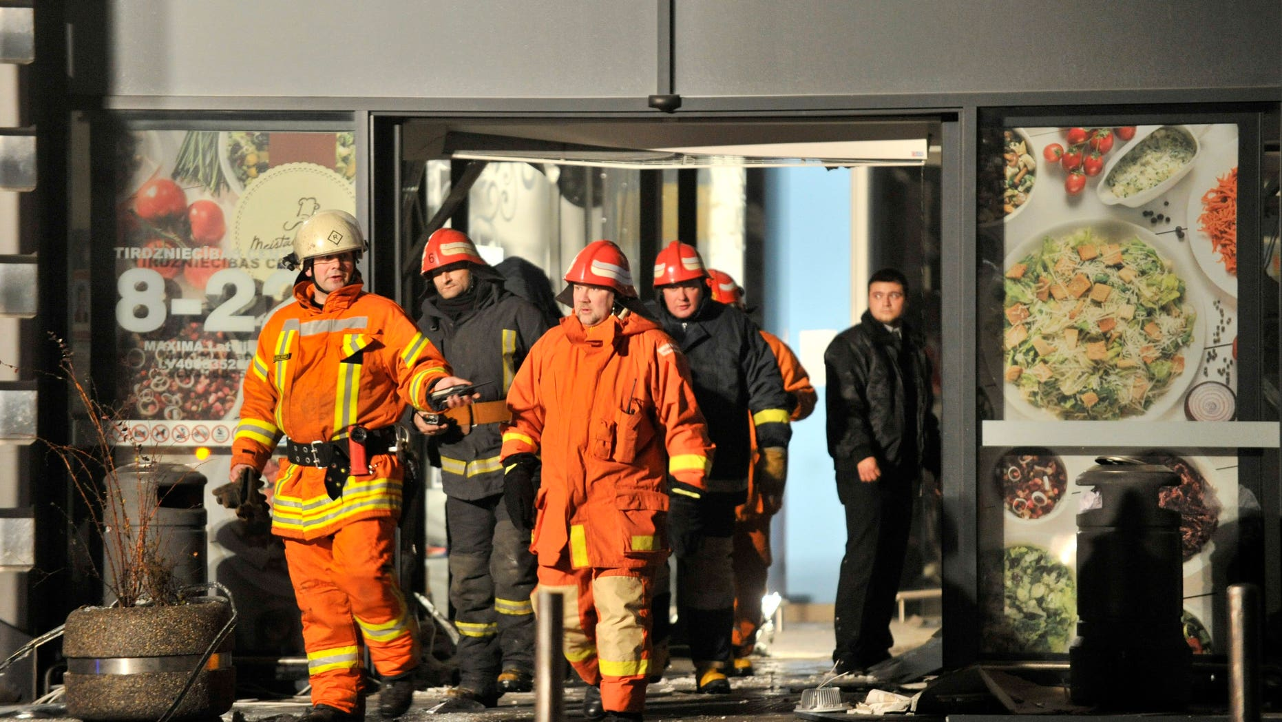 Rescuers work at the Maxima grocery store after its roof collapsed in Riga, Latvia, Thursday, Nov. 21, 2013. Latvian rescue officials say a roof at a large grocery store in the country's capital collapsed and killed several people  and injuring more than a dozen people.  (AP Photo/Roman Koksarov)