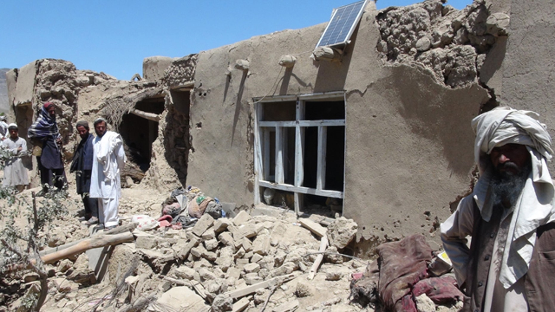 June 6, 2012: Afghan villagers gather near a house destroyed in an apparent NATO raid in Logar province, south of Kabul, Afghanistan.