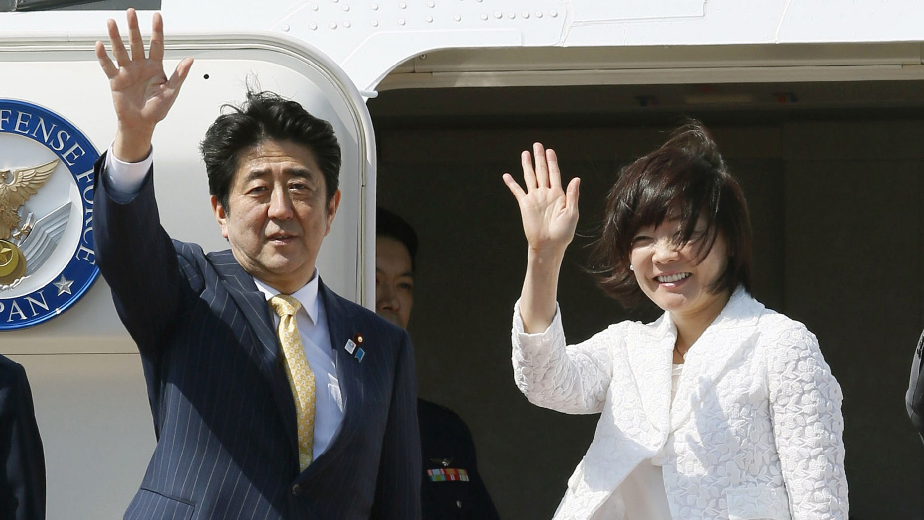 Japanese Prime Minister Shinzo Abe and his wife Akie wave before boarding a plane at Tokyo's Haneda Airport Friday, May 24, 2013. Abe is traveling to Myanmar for a three-day trip, the first visit to the country by a Japanese leader in 36 years. (AP Photo/Kyodo News)  JAPAN OUT, MANDATORY CREDIT