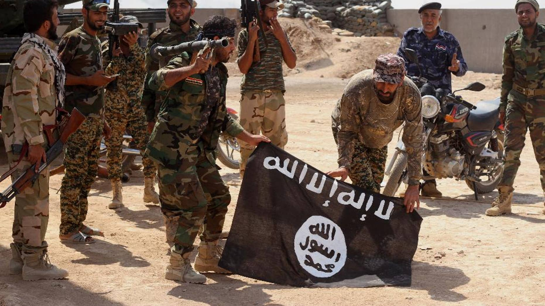 Sept. 1, 2014: Iraqi security forces hold a flag of the Islamic State group they captured during an operation outside Amirli, some 105 miles north of Baghdad, Iraq. (AP)