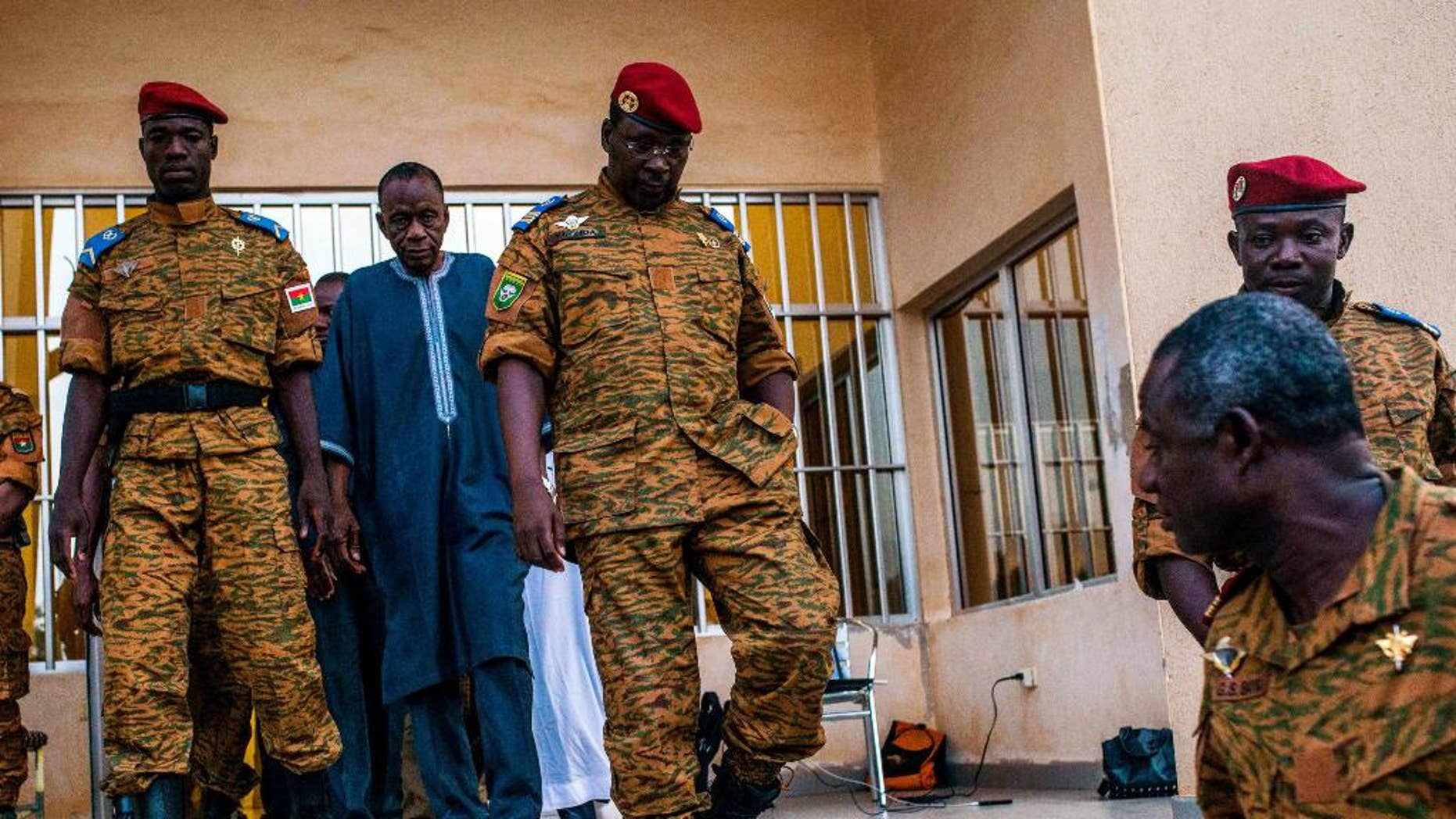Burkina Faso Lt. Col. Issac Yacouba Zida, center, leaves a government building after meeting with political leaders in Ouagadougou, Burkina Faso, Tuesday, Nov. 4, 2014. International envoys tried Tuesday to resolve Burkina Faso's political crisis, with the specter of a power vacuum looming after the country's longtime president fled last week. (AP Photo/Theo Renaut)