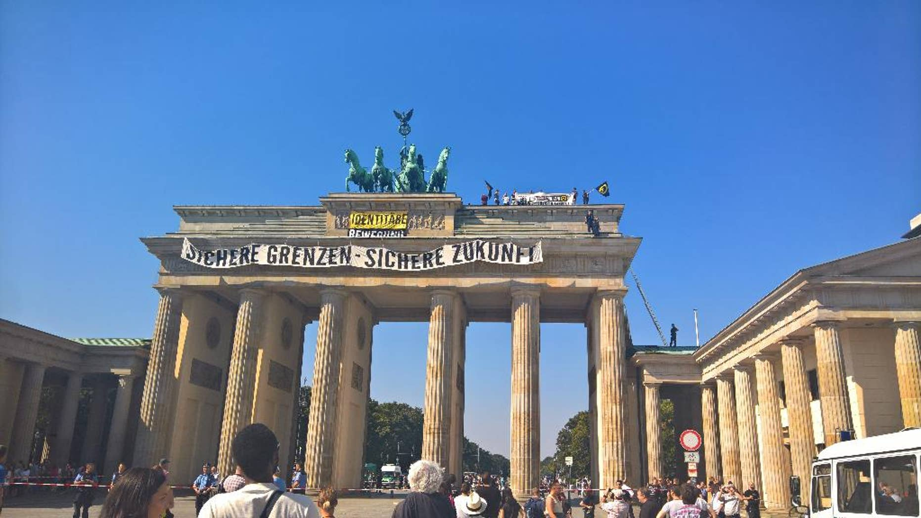 """Anti-Islam activists have staged an hour-long demonstration atop Berlin's Brandenburg Gate Saturday Aug. 27, 2016. The protesters unfurled a banner calling for """"secure borders"""" in Germany. Police said 15 people were briefly detained over the protest and are likely to face charges of trespassing, harassment and breaching laws on public assembly Banner reads : Secure Borders - Secure Future. (AP Photo Frank Jordans)"""