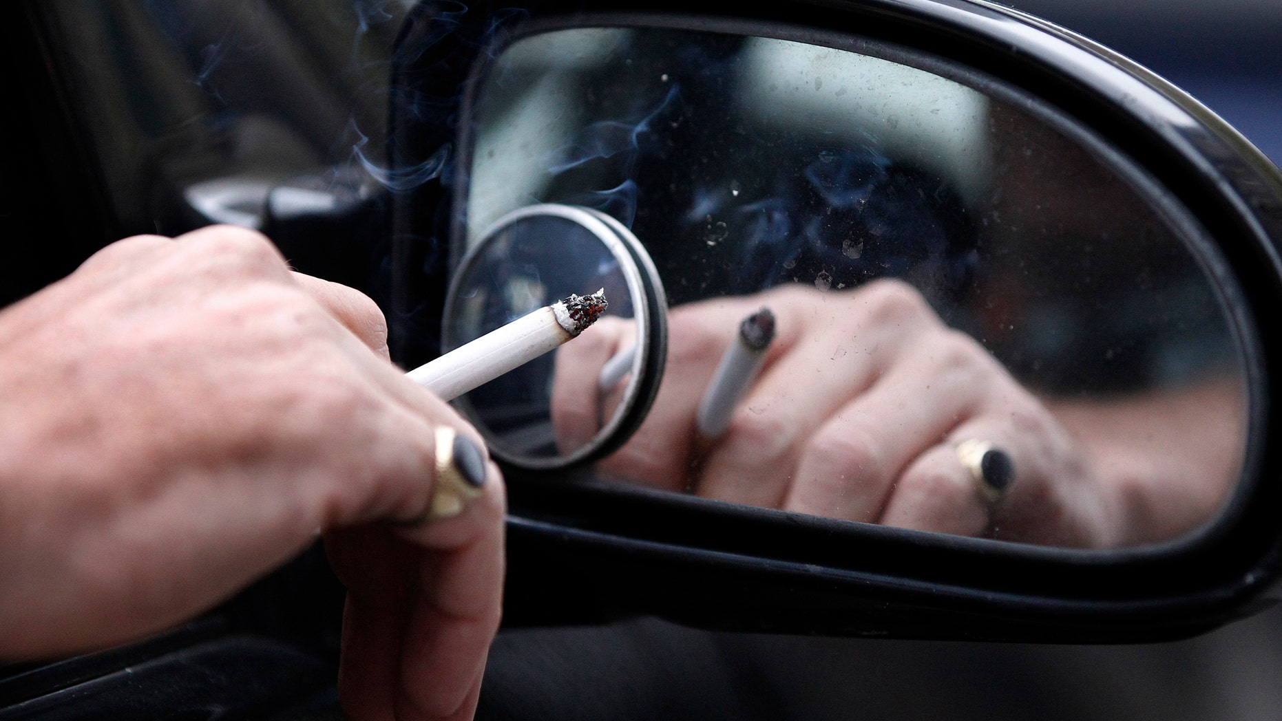 A man smokes a cigarette as he sits in his car. (REUTERS/Phil Noble)