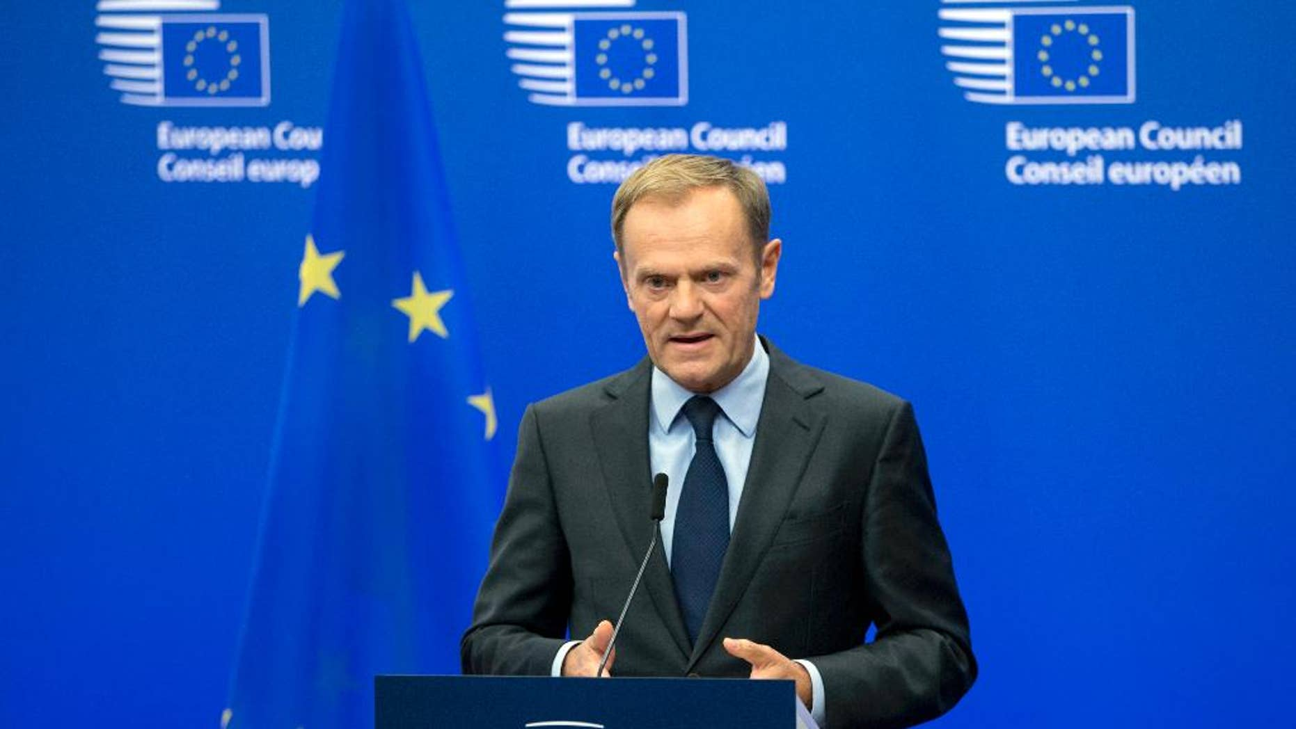 FILE- In this Wednesday, Nov. 9, 2016 file photo, European Council President Donald Tusk reads a statement during a media conference at the EU Council building in Brussels. Tusk says he thinks the European Union will extend sanctions against Russia, but that it will be harder to preserve the West's unity on Moscow when Donald Trump is U.S. president. (AP Photo/Virginia Mayo, File)