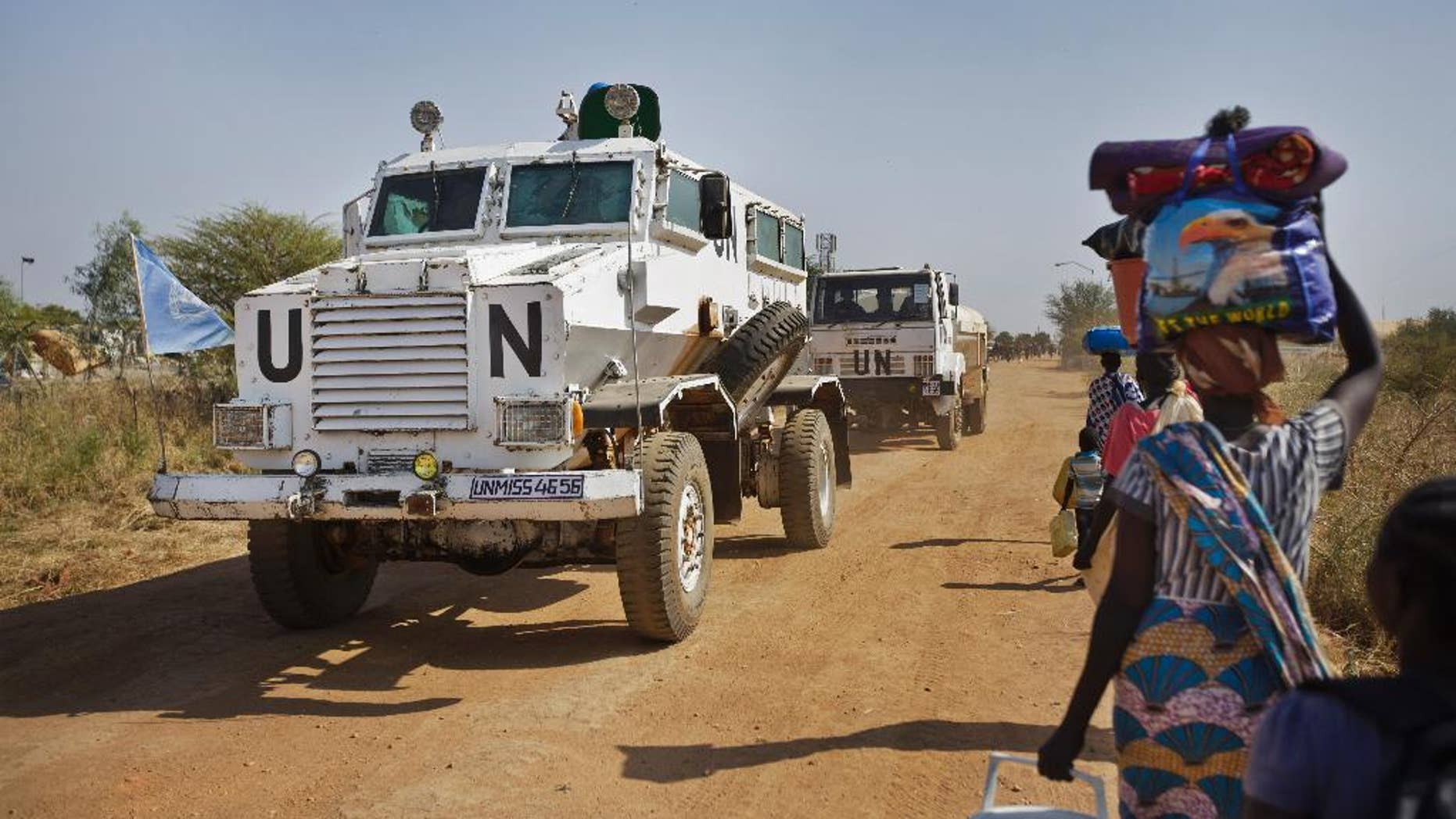 A United Nations armored vehicle passes people walking towards the U.N. camp in Malakal, South Sudan, in 2013.