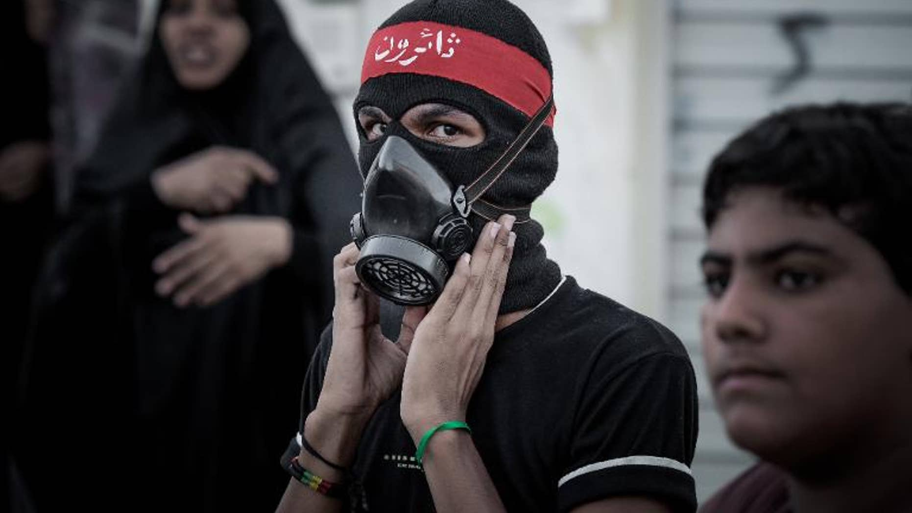 A Bahraini protester poses for a picture during clashes with riot police in the village of al-Maqsha, on September 21, 2013