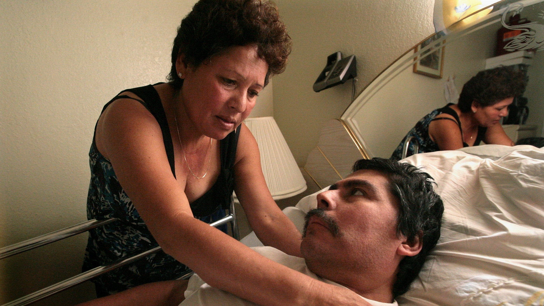 Oct. 13, 2008: Lucila Huerta, tends to her husband Guadalupe, who is suffering from Valley Fever and other medical problems, in their apartment in Madera, Calif.