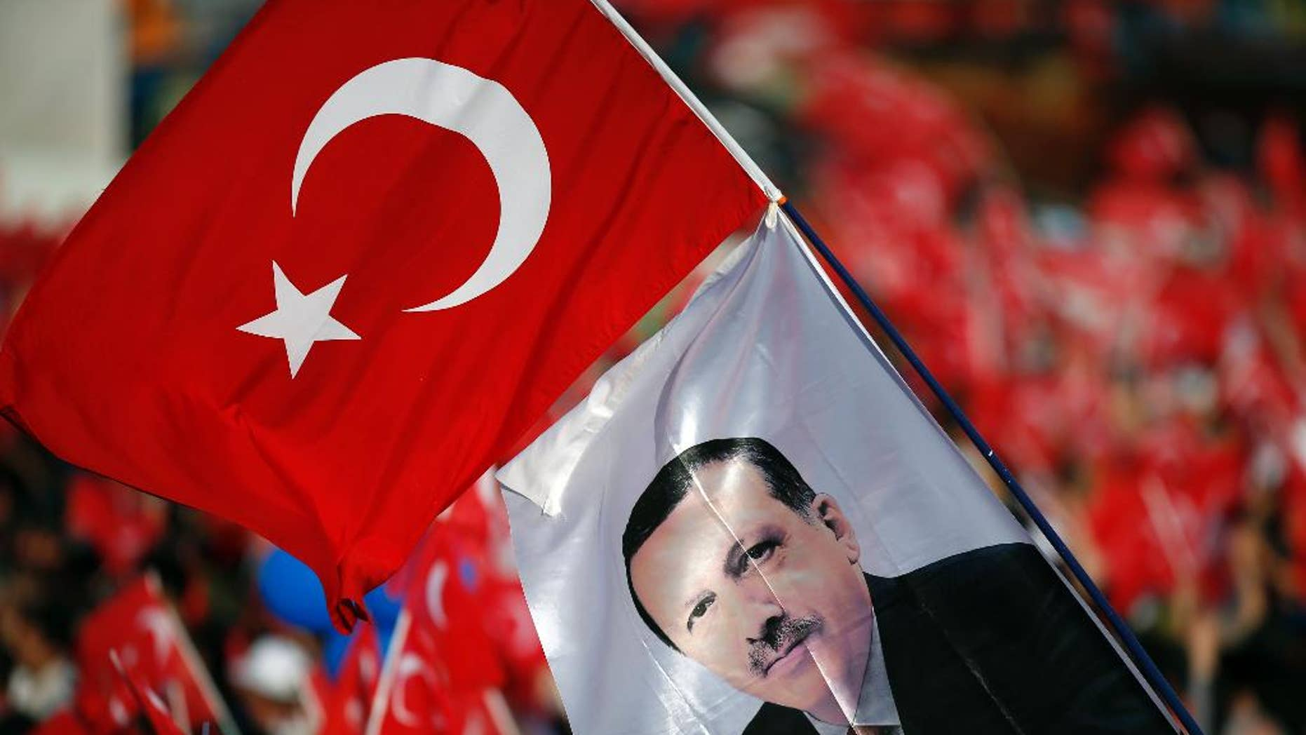 People wave national flags with an image of Turkey's President Recep Tayyip Erdogan during celebrations marking the 563rd anniversary of the Ottoman conquest of Constantinople, now Istanbul, in Istanbul, Turkey, Sunday, May 29, 2016. (AP Photo/Emrah Gurel)
