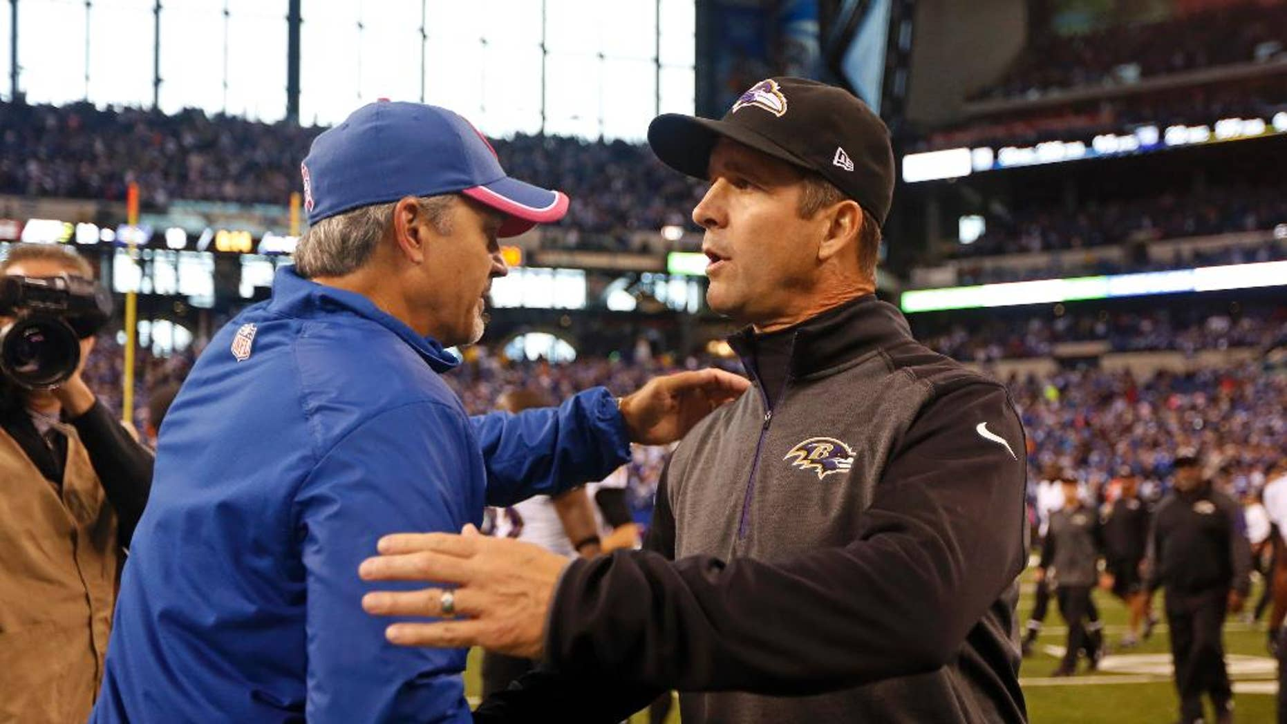 Indianapolis Colts head coach Chuck Pagano, left, greets Baltimore Ravens head coach John Harbaugh following an NFL football game in Indianapolis, Sunday, Oct. 5, 2014. The Colts defeated the Ravens 20-13. (AP Photo/Jeff Roberson)