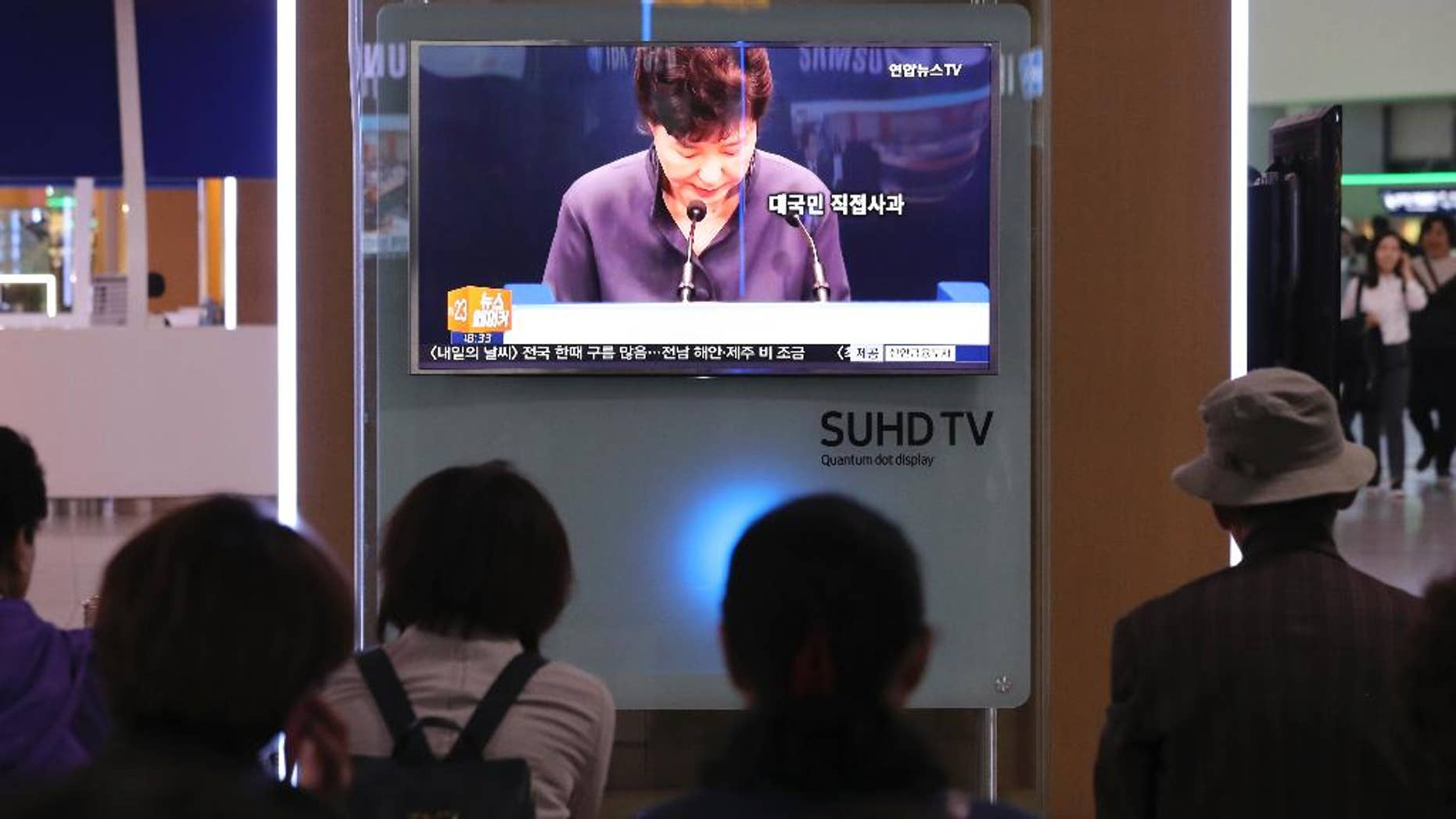 In this Oct. 25, 2016 photo, people watch a TV screen showing the news program about South Korean President Park Geun-hye's apology, at Seoul Railway Station in Seoul, South Korea. To outsiders, the frenzy that has erupted here may not seem to match this week's acknowledgment by South Korean President Park that she got help, including the editing of some of her speeches, from a mysterious woman outside of the government.  But Park's surprise televised address has created one of the biggest challenges of her four years in power - and touched a deep chord in this divided nation.  (AP Photo/Lee Jin-man)
