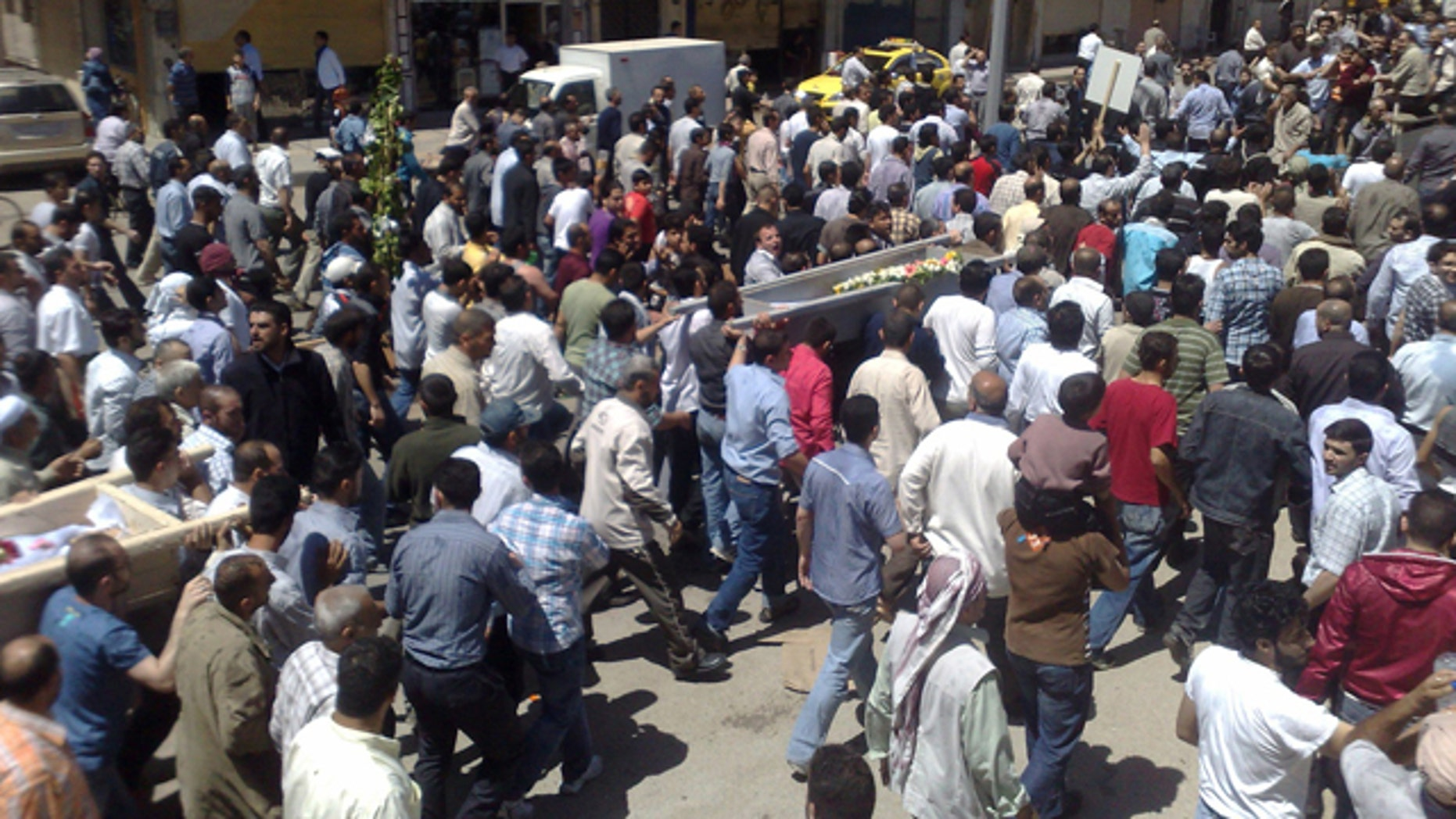 May 21: In this citizen journalism image made on a mobile phone and acquired by the AP, Syrian anti-government supporters carry the coffins of people whom they say were killed in the government crackdown, in the central city of Homs, Syria.