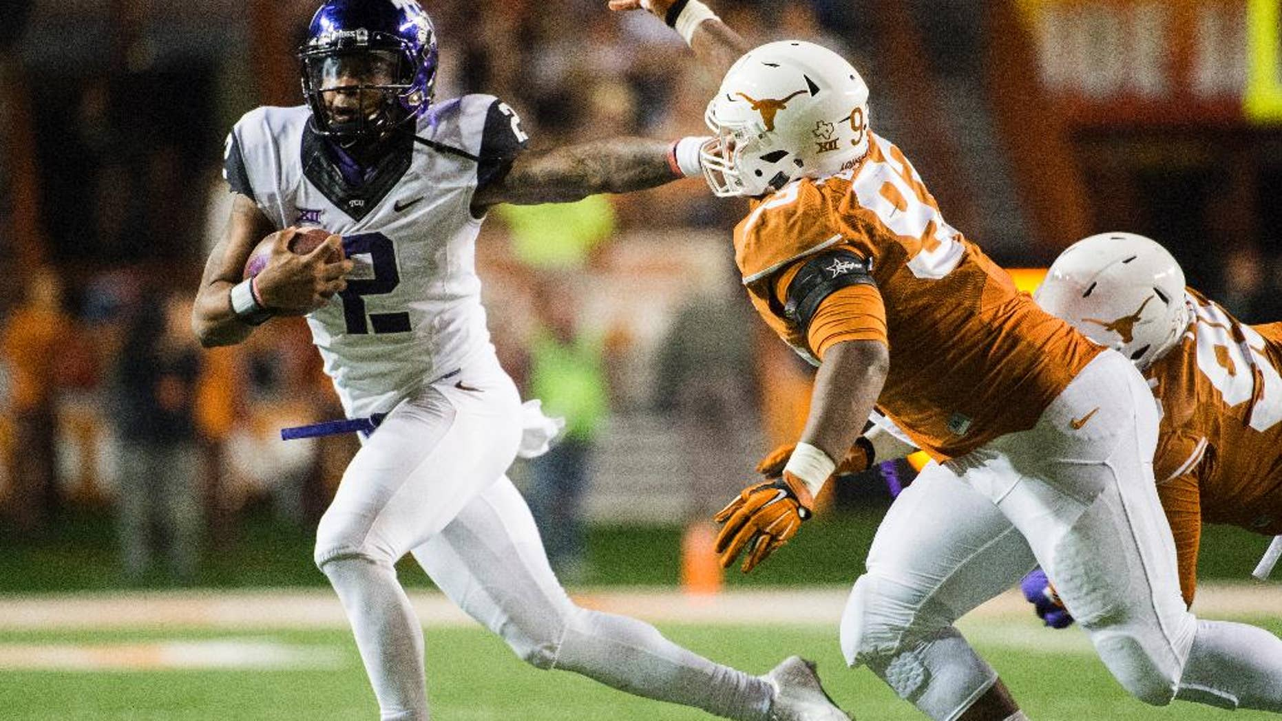 CORRECTS NAME OF TCU PLAYER TO TREVONE BOYKIN -  TCU's Trevone Boykin (2) holds off Texas' Paul Boyette Jr. (93) during the second half of an NCAA college football game, Thursday, Nov. 27, 2014, in Austin, Texas. (AP Photo/Ashley Landis)