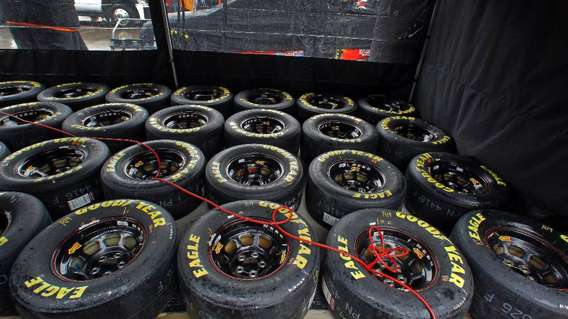 Tires sit under a tent as rain falls before a NASCAR Sprint Cup Series auto race at Bristol Motor Speedway on Sunday, April 19, 2015, in Bristol, Tenn. (AP Photo/Wade Payne)