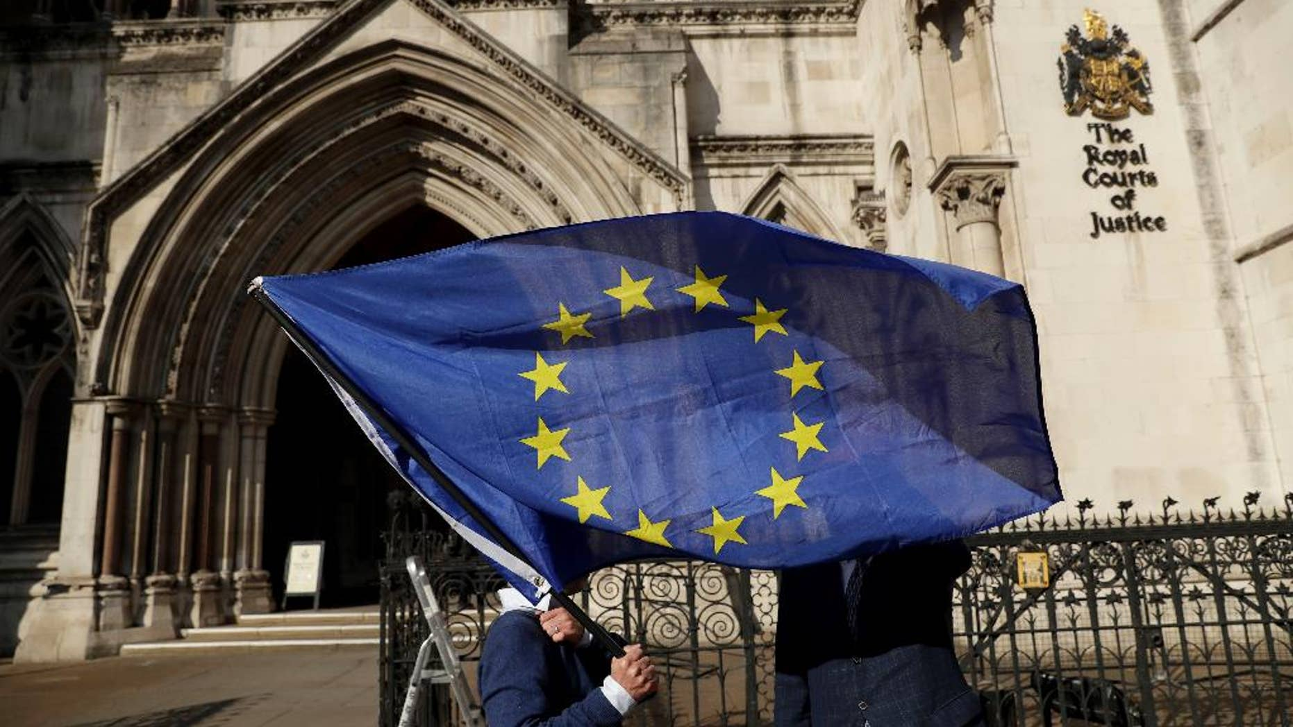Pro-EU membership supporter Phil Jones holds an EU flag outside the High Court, on the first day of the lawsuit of Gina Miller, a founder of investment management group SCM Private, in London, Thursday, Oct. 13, 2016. Rival protesters have gathered outside the High Court in London, where lawyers are battling over whether the government has the power to trigger Britain's exit from the European Union without approval from Parliament. (AP Photo/Matt Dunham)