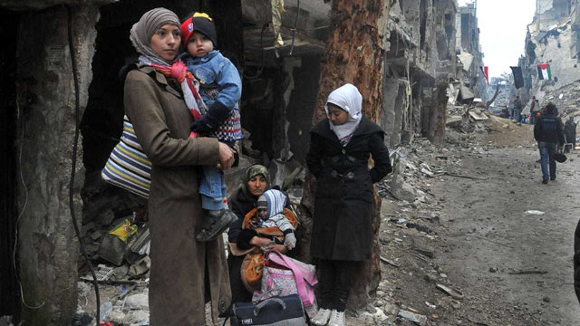 February 4, 2014: In this photo released by the Syrian official news agency SANA, residents of the besieged Yarmouk Palestinian refugee camp wait to leave the camp, on the southern edge of Damascus. Over the past six days the U.N. continued to distribute food parcels in the Palestinian camp where activists say at least 85 people have died as a result of lack of food and medicine since mid-2013. (AP Photo/SANA)