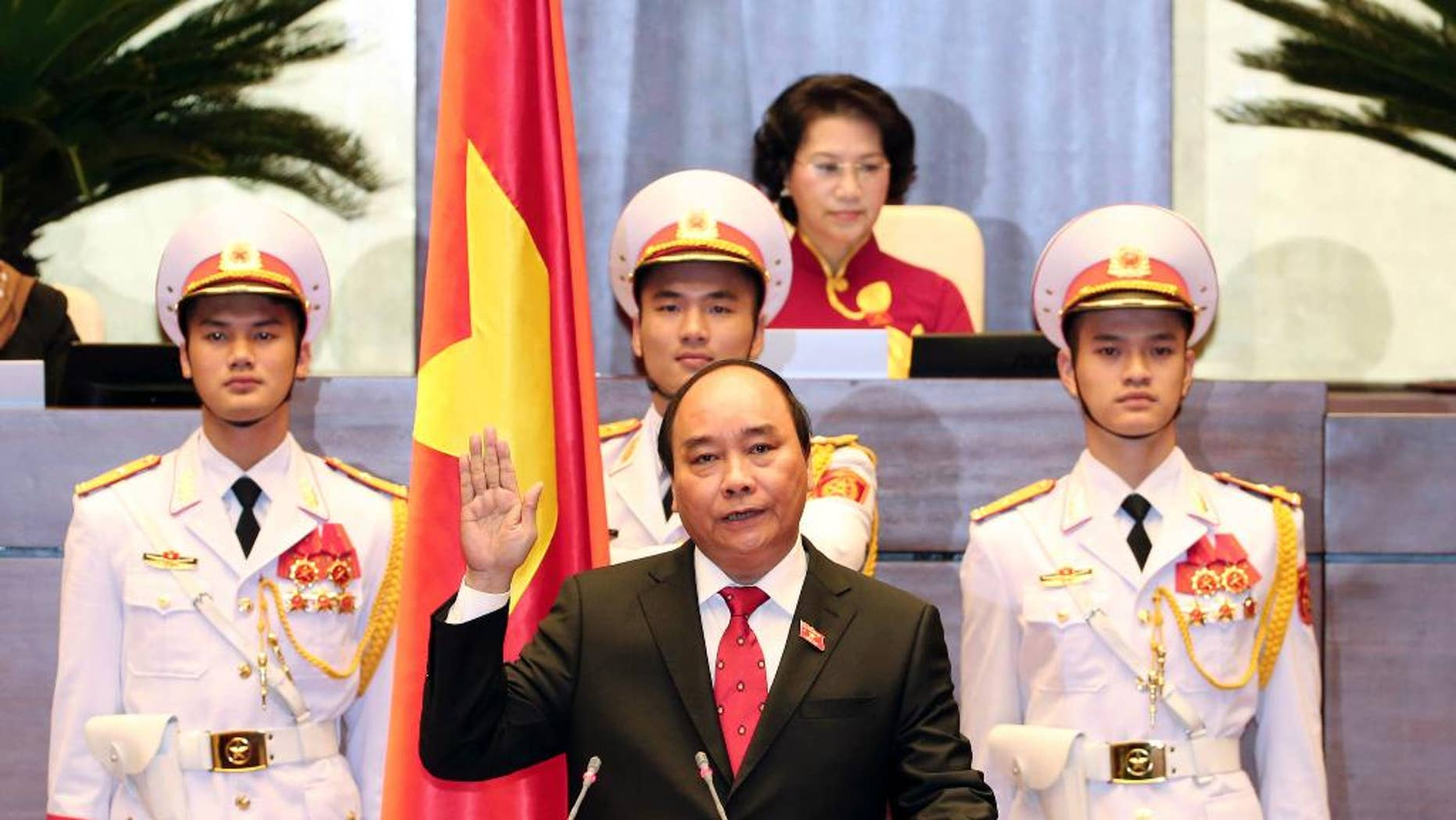 Nguyen Xuan Phuc, center, takes oath after being elected as prime minister in Hanoi, Vietnam Thursday April, 7, 2016. Vietnam's National Assembly on Thursday elected Phuc as prime minister, and he takes office at a time of soaring public debt, a serious budget deficit and China's growing assertiveness in the South China Sea. (Thong Nhat/Vietnam News Agency via AP)