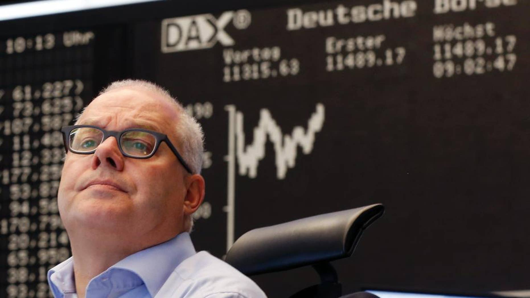 A trader watches his screens at the stock market in Frankfurt, Germany, Monday, July 13, 2015. Global stock markets bounced higher Monday after Greece and its European creditors agreed on a bailout deal, substantially reducing the uncertainty about Greece's future in the euro common currency. (AP Photo/Michael Probst)
