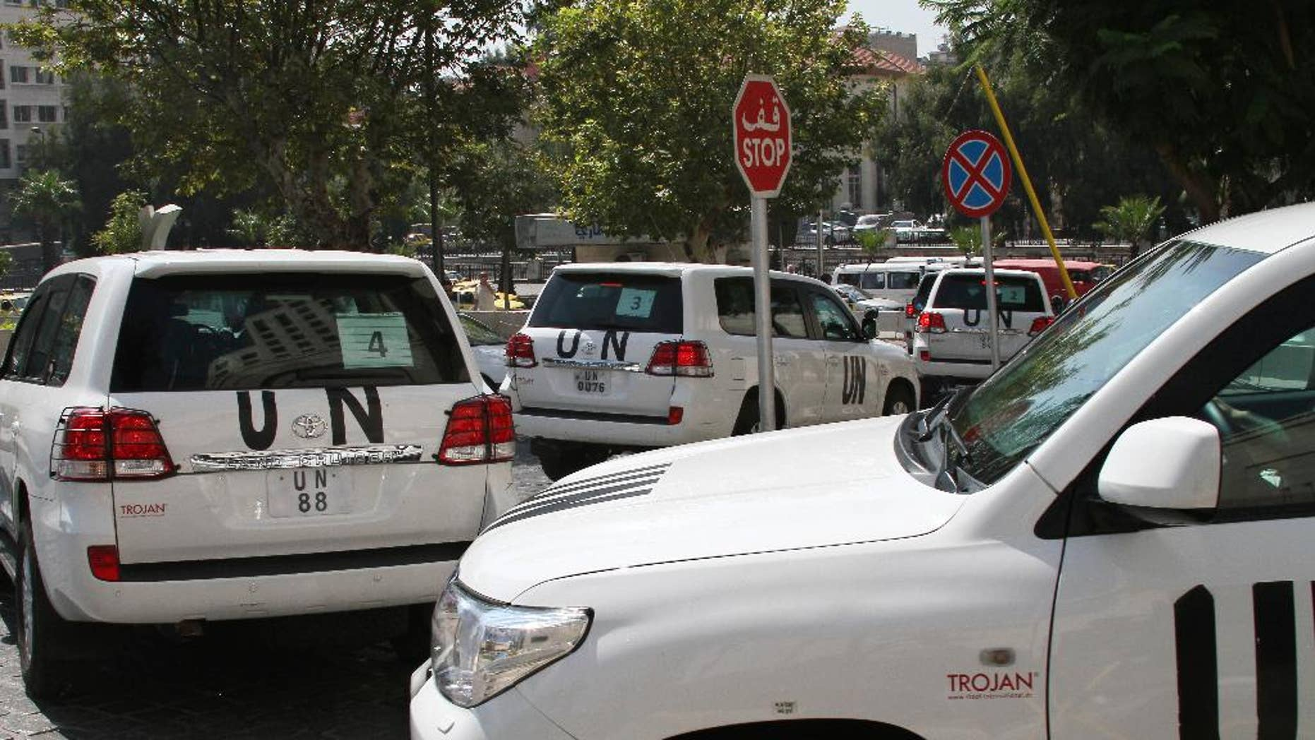 FILE -- In this August 26, 2013, file Photo, a U.N. team, that is scheduled to investigate an alleged chemical attack that killed hundreds last week in a Damascus suburb, leaves their hotel in a convoy, in Damascus, Syria. In a  statement issued Tuesday, May 27, 2014, by the chemical weapons watchdog that is overseeing the dismantling of Syria's chemical weapons program, said a convoy of its inspectors has come under attack, but all are safe.  The Organization for the Prohibition of Chemical Weapons said that the inspectors had been traveling to the site of an alleged chlorine gas attack site when they were attacked. (AP Photo, File)