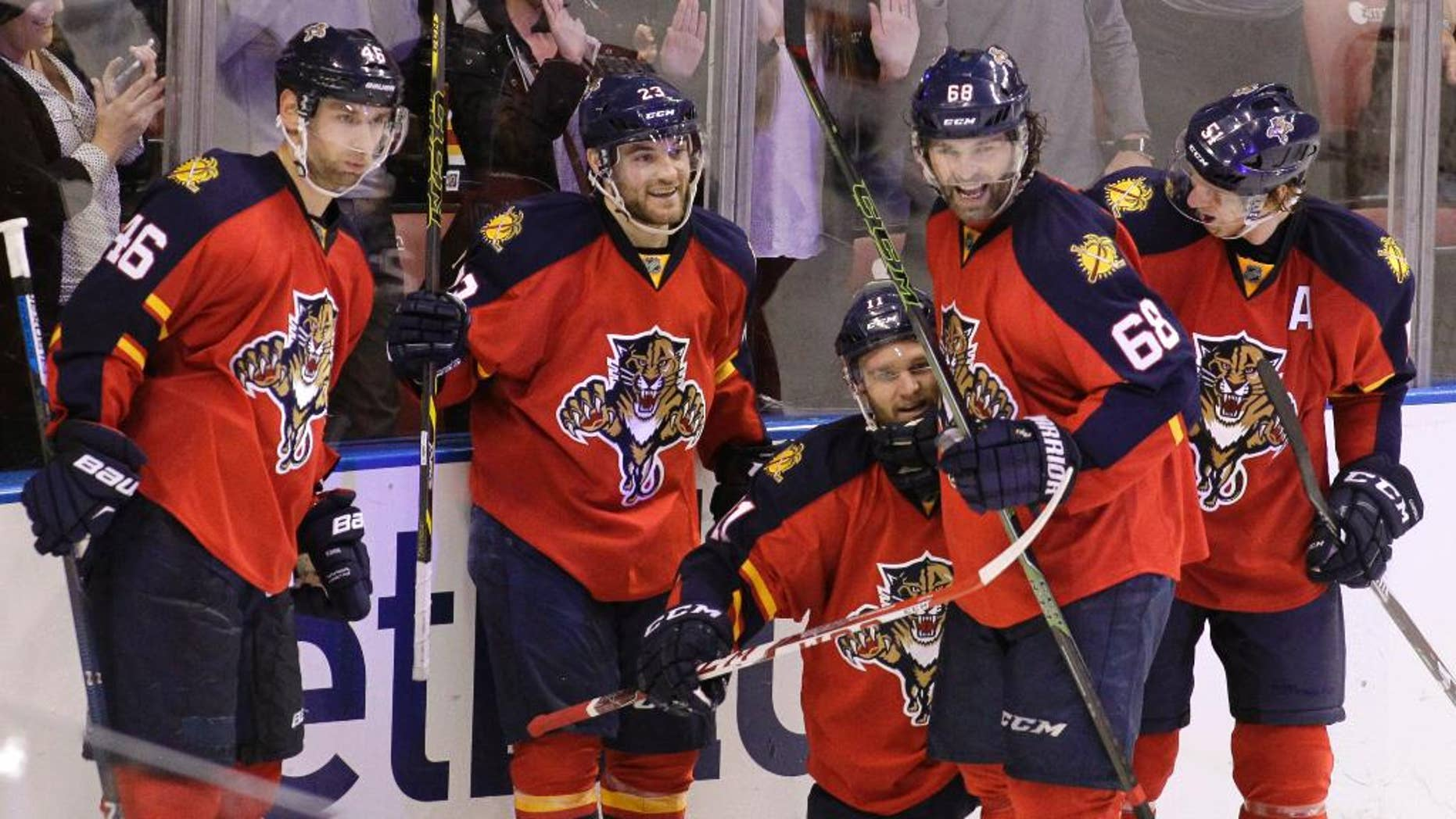 Florida Panthers' Jonathan Huberdeau, third from left, celebrates with teammates Jakub Kindl (46), of the Czech Republic,  Rocco Grimaldi, second from left, Jaromir Jagr (68), of the Czech Republic, and Brian Campbell, right, after scoring a goal during the third period of an NHL hockey game against the New Jersey Devils, Thursday, March 31, 2016, in Sunrise, Fla. The Panthers won 3-2. (AP Photo/Luis M. Alvarez)