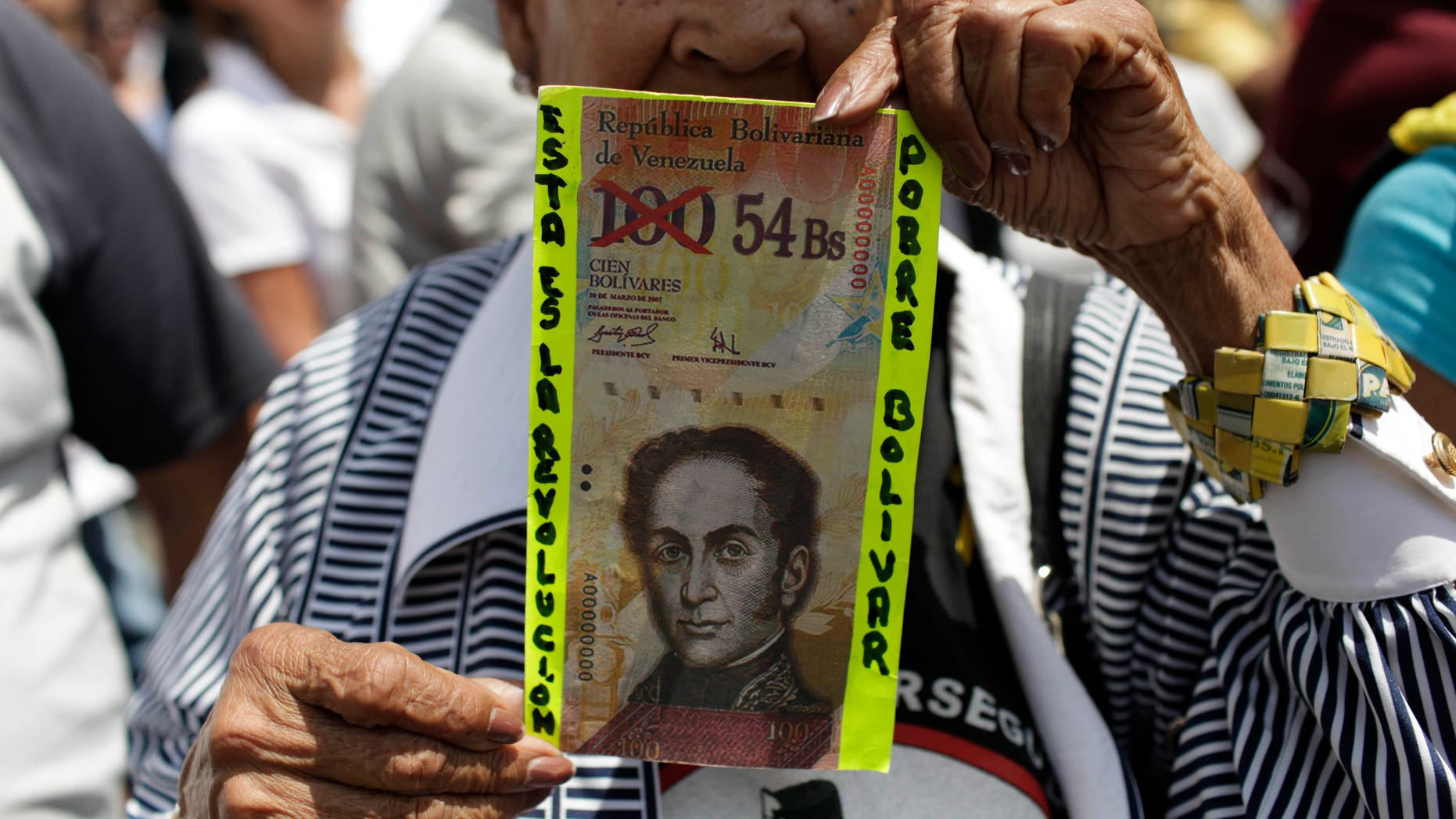 """FILE - In this Feb. 23, 2013 file photo, an anti-government protester in Caracas holds up a fake Venezuelan banknote that reads in Spanish, """"This is the revolution. Poor Bolivar,"""" with the value of 100 crossed out and 54 written next to it. Venezuelans have been scrambling for dollars as their bolivar currency is in free fall, selling on the black market for a tenth its official value. In response, the government is trying to block access to websites that Venezuelans use to track the black market exchange rate. (AP Photo/Ariana Cubillos, File)"""