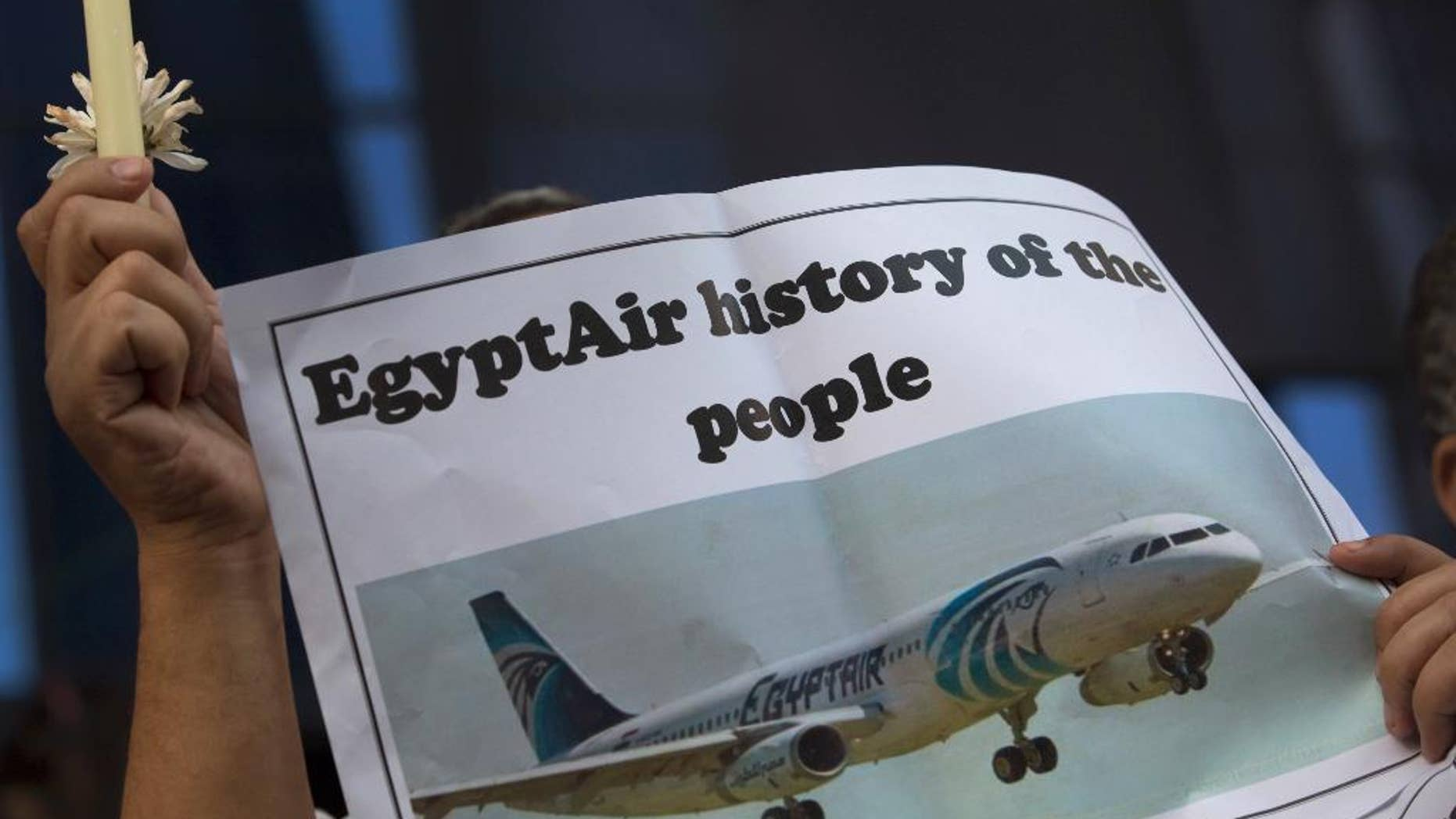 FILE - In this May 24, 2016 file photo, an Egyptian journalist holds a candle and a poster supporting EgyptAir during a candlelight vigil for the victims of EgyptAir flight 804 in front of the Journalists' Syndicate in Cairo, Egypt. Egypt on Wednesday, June 15, 2016, said that it spotted and obtained images from the wreckage of the EgyptAir plane flying from Paris to Cairo that crashed into the Mediterranean last month, killing all 66 people on board, according to a statement by the country's investigation committee.  (AP Photo/Amr Nabil, File)