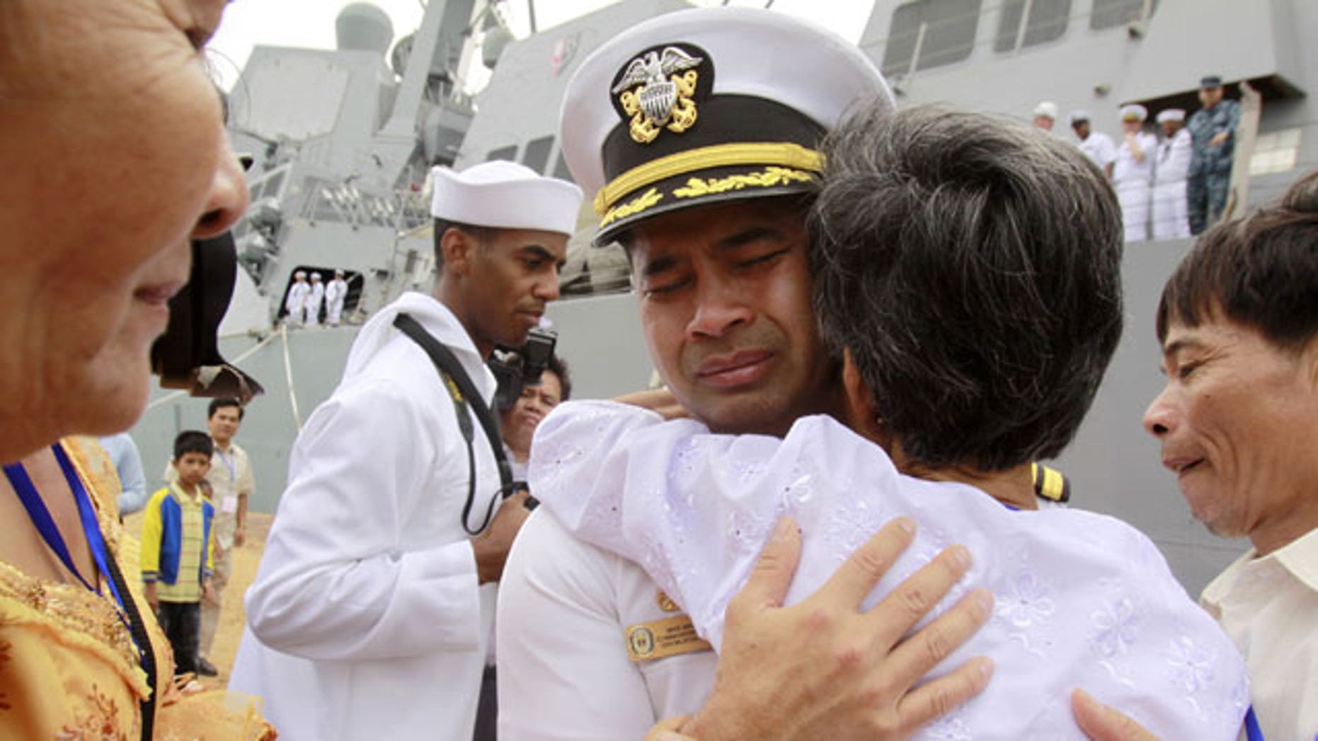 """December 3, 2010: U.S. navy officer Michael """"Vannak Khem"""" Misiewicz becomes emotional as he embraces his aunt Samrith Sokha, 72, at Cambodian coastal international see port of Sihanoukville, Cambodia. Misiewicz passed confidential information on ship routes to Malaysian businessman Leonard Francis' Singapore-based company, Glenn Defense Marine Asia Ltd., or GDMA, according to court documents. (AP)"""