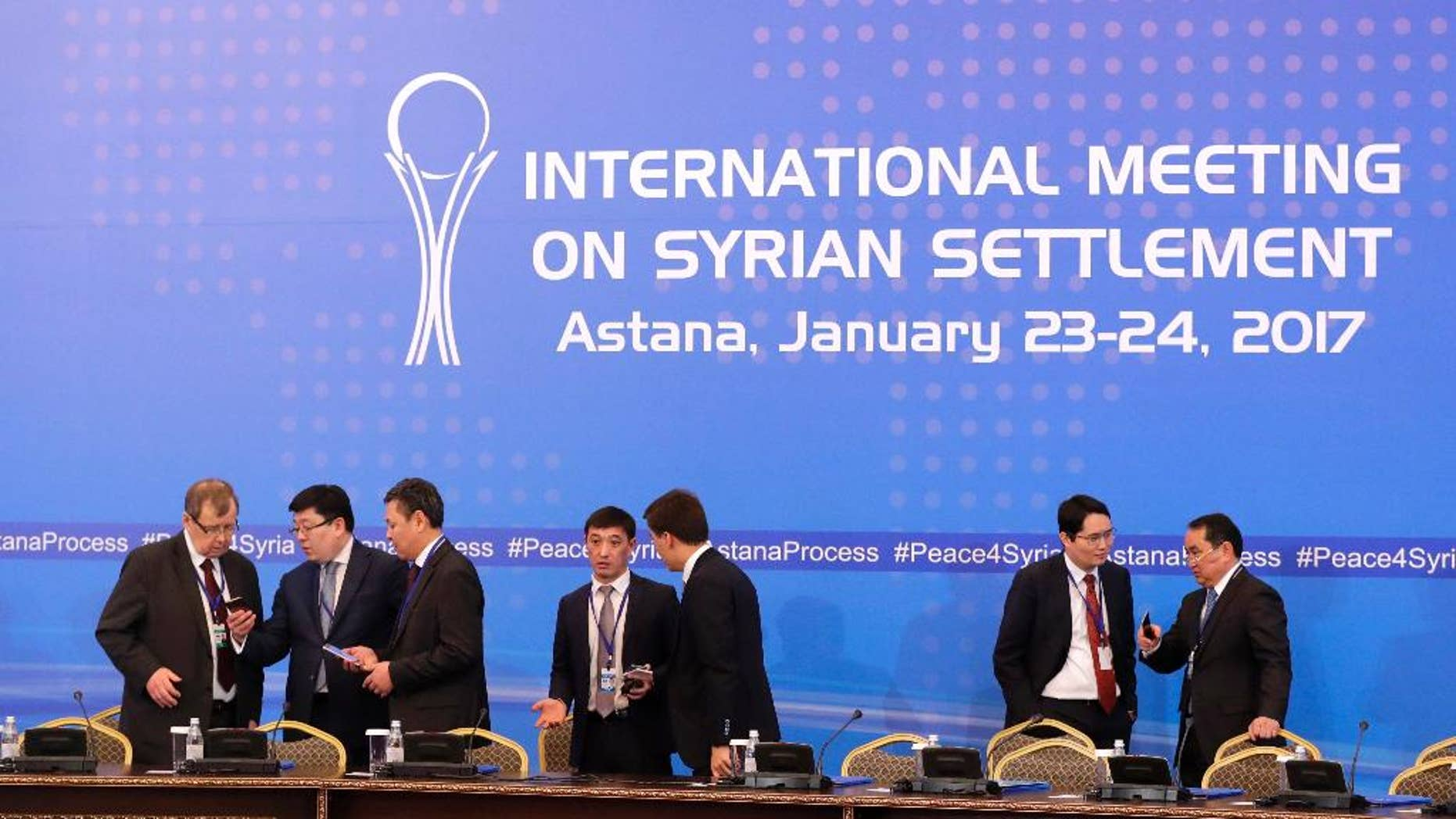 Kazakhstan's officials prepare working space for delegations at a hotel lobby where Russia, Iran and Turkey will hold talks on Syrian peace, in Astana, Kazakhstan, Monday, Jan. 23, 2017. The talks are the latest attempt to forge a political settlement to end a war that has by most estimates killed more than 400,000 people since March 2011 and displaced more than half the country's population. (AP Photo/Sergei Grits)