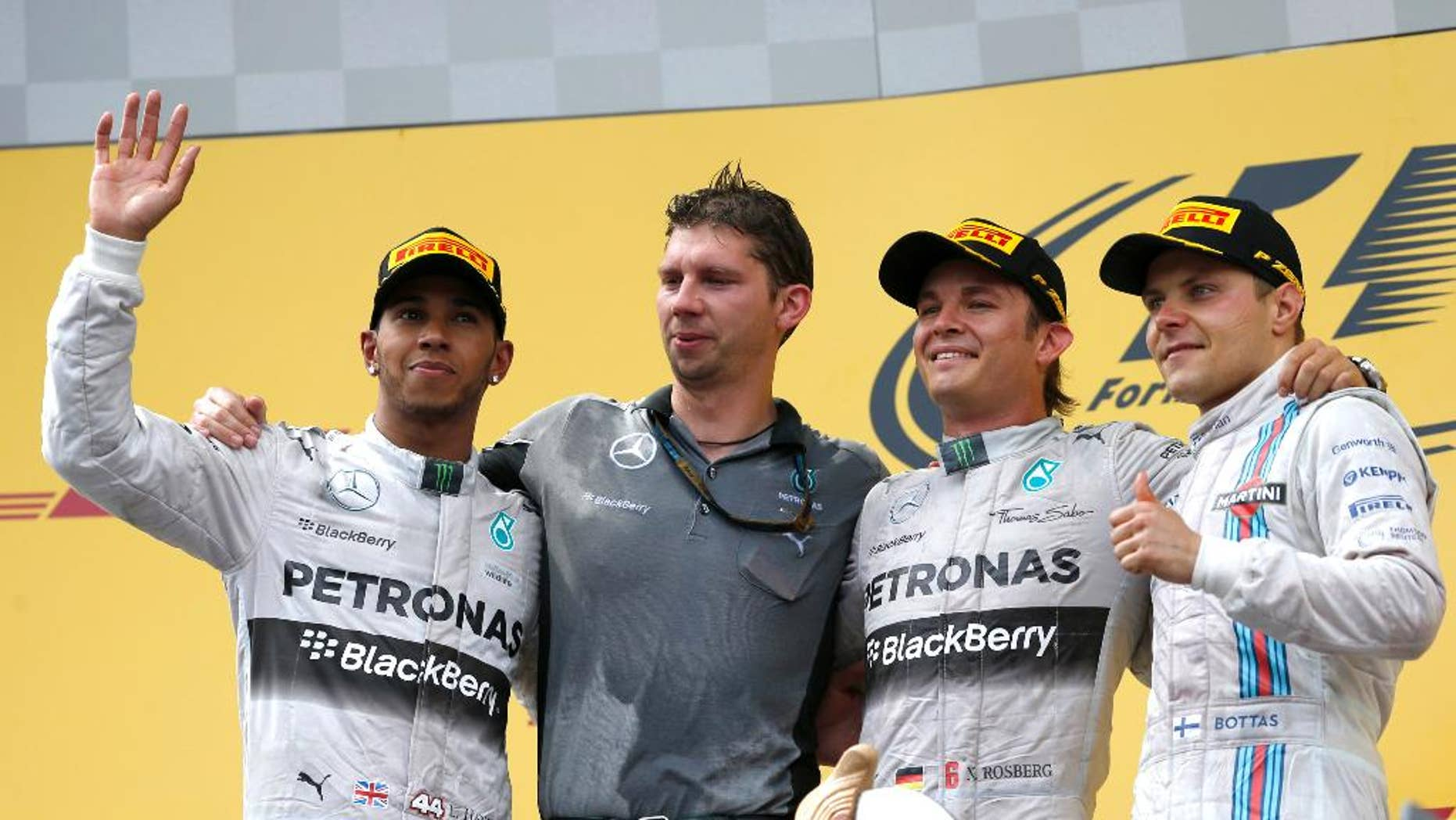 Mercedes driver Nico Rosberg of Germany, second from right, celebrates winning on the podium with team member James Vowles, second from left, second placed Mercedes driver Lewis Hamilton of Britain, left and third placed Williams driver Valtteri Bottas of Finland, after the Austrian Formula One Grand Prix race at the Red Bull Ring in Spielberg, Austria, Sunday, June 22, 2014. (AP Photo/Darko Vojinovic)