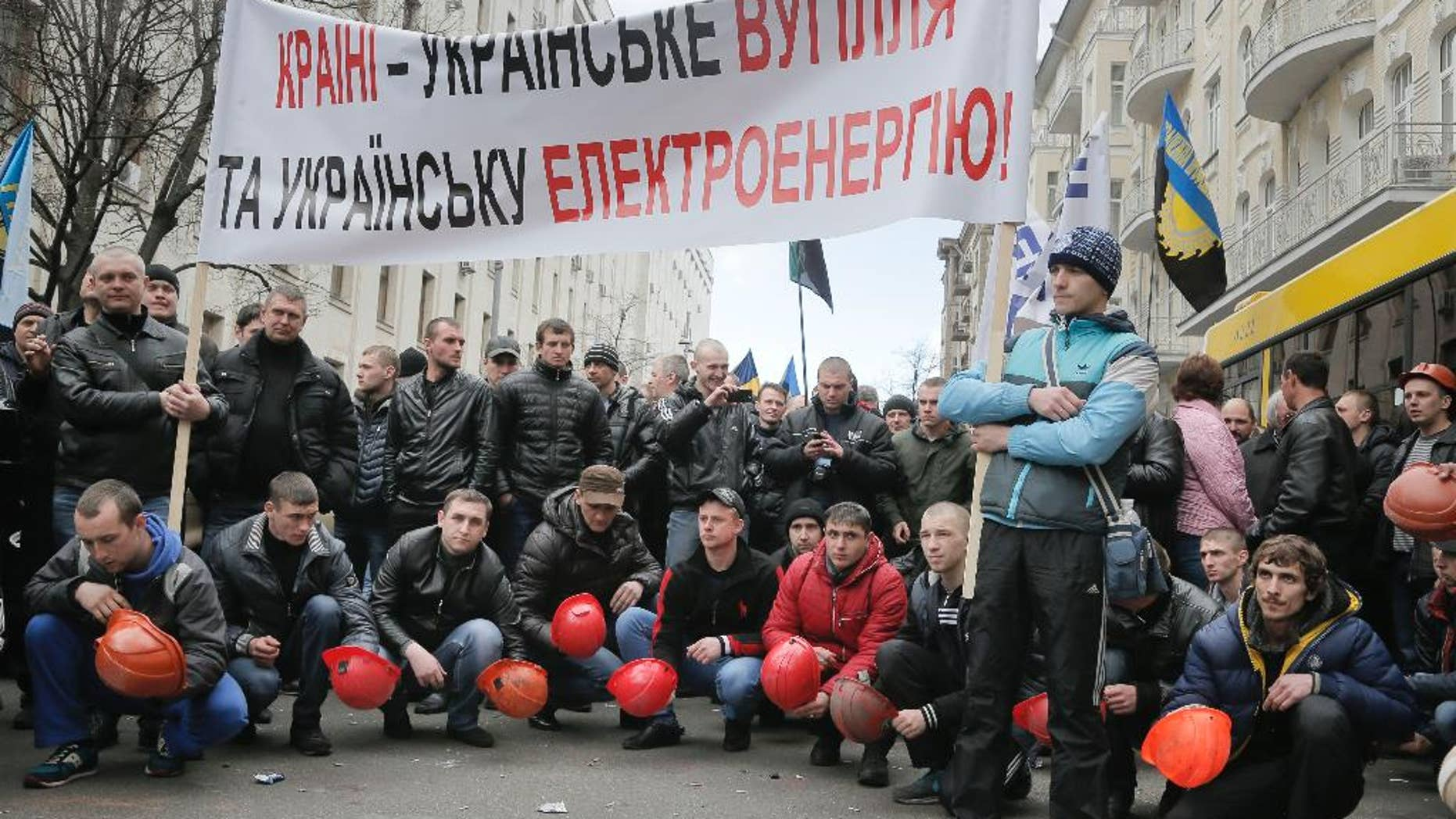Ukrainian miners bang their helmets on the pavement during a protest outside the presidential administration in Kiev, Ukraine, Wednesday, April 22. 2015. About 1,000 miners gathered near government buildings in a call for the resignation of the energy minister amid anger at the authorities decision to buy coal from abroad. The banner reads: 'Ukrainian Coal and Ukrainian Electricity for the Country.' (AP Photo/Efrem Lukatsky)