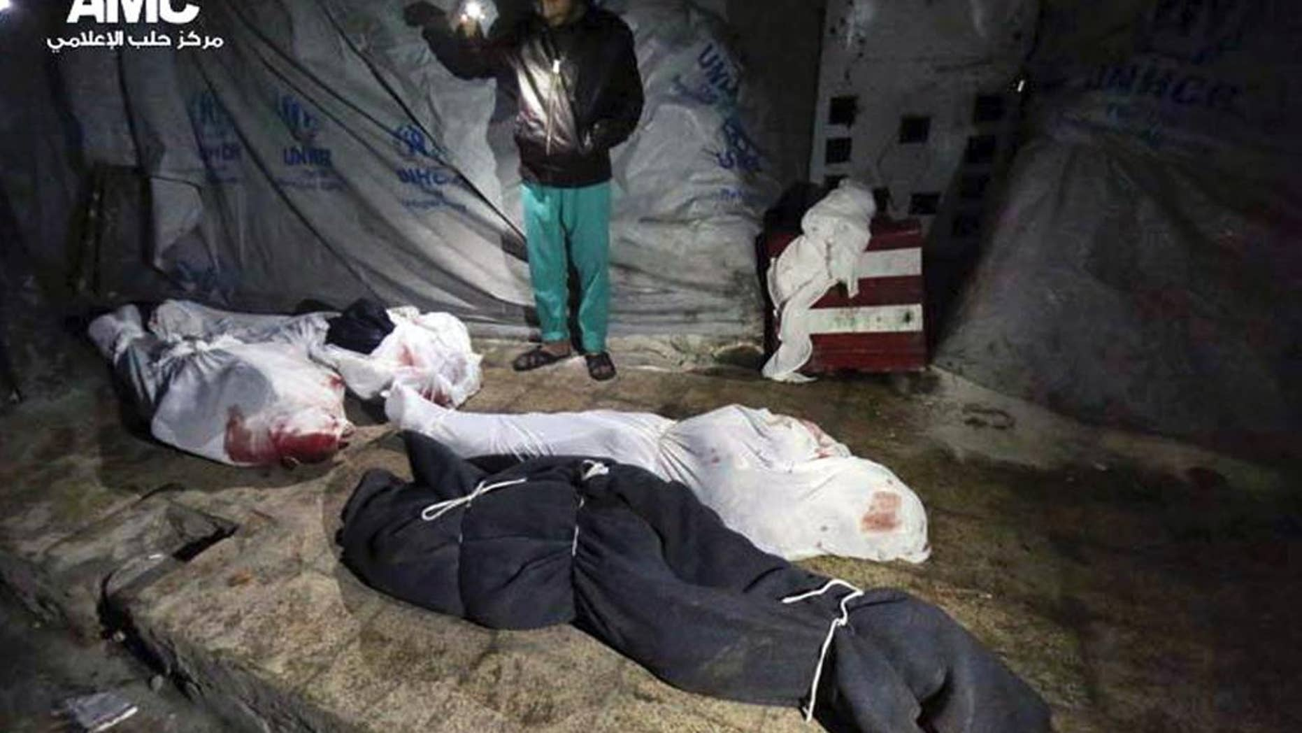 Feb. 5, 2015 - Syrian man stands next to bodies that were, according to activists, killed from an airstrike by the Syrian government forces in Aleppo, Syria. Syrian army helicopters dropped 2 barrel bombs on a crowded square in the northern city of Aleppo, killing tens of civilians as they sat on a bus and collected water, activists said Friday.