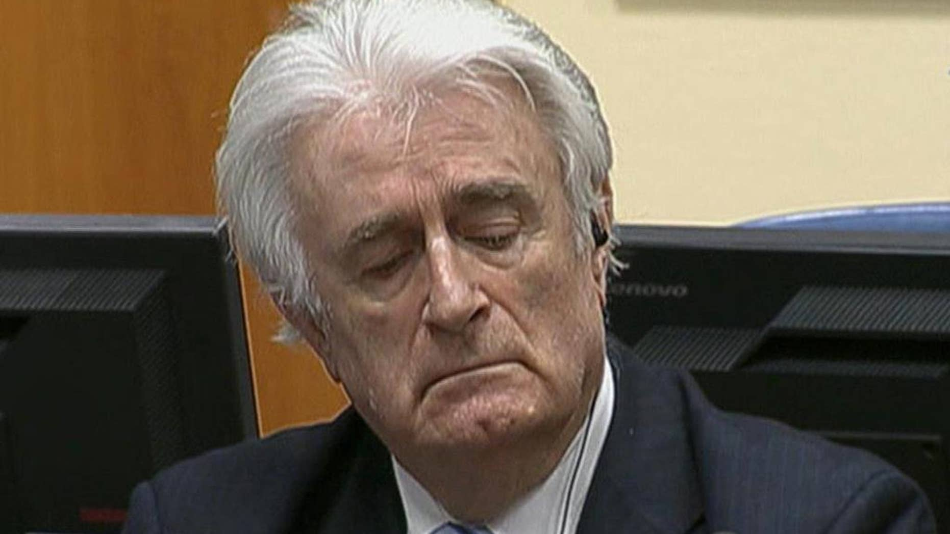 In this image taken from video Bosnian Serb wartime leader Radovan Karadzic listens to the his sentence  at the International Criminal Tribunal for Former Yugoslavia (ICTY) in The Hague, The Netherlands Thursday March 24, 2016. Karadzic was convicted of genocide and nine other charges Thursday at a U.N. court, and sentenced to 40 years in prison. (ICTY, Pool via AP)